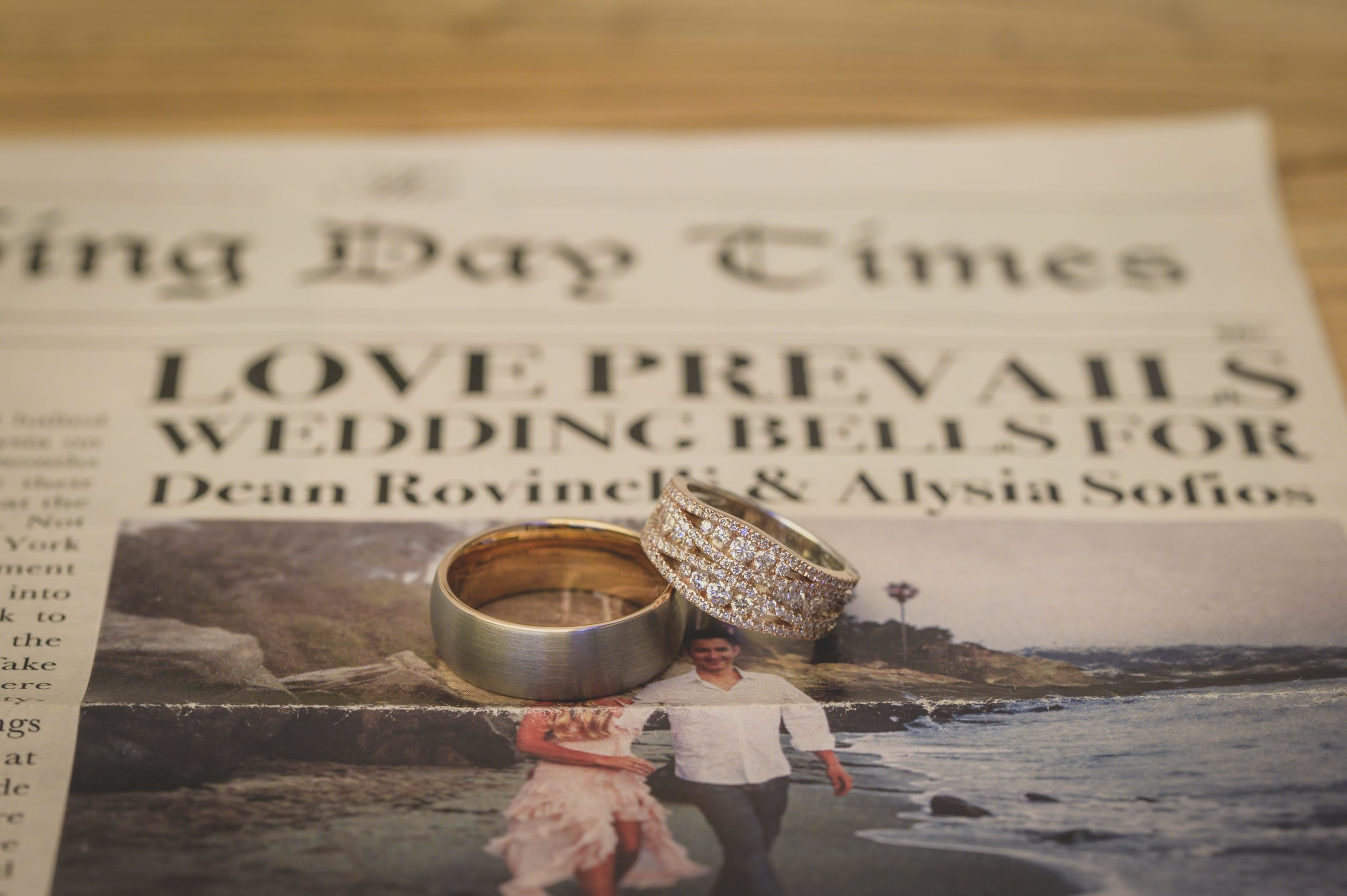 Wedding Photography Packages - Heritage Park, Dana Point, CA - Wedding bands on top of a local newspaper with the headline story showing the newly engaged couple.