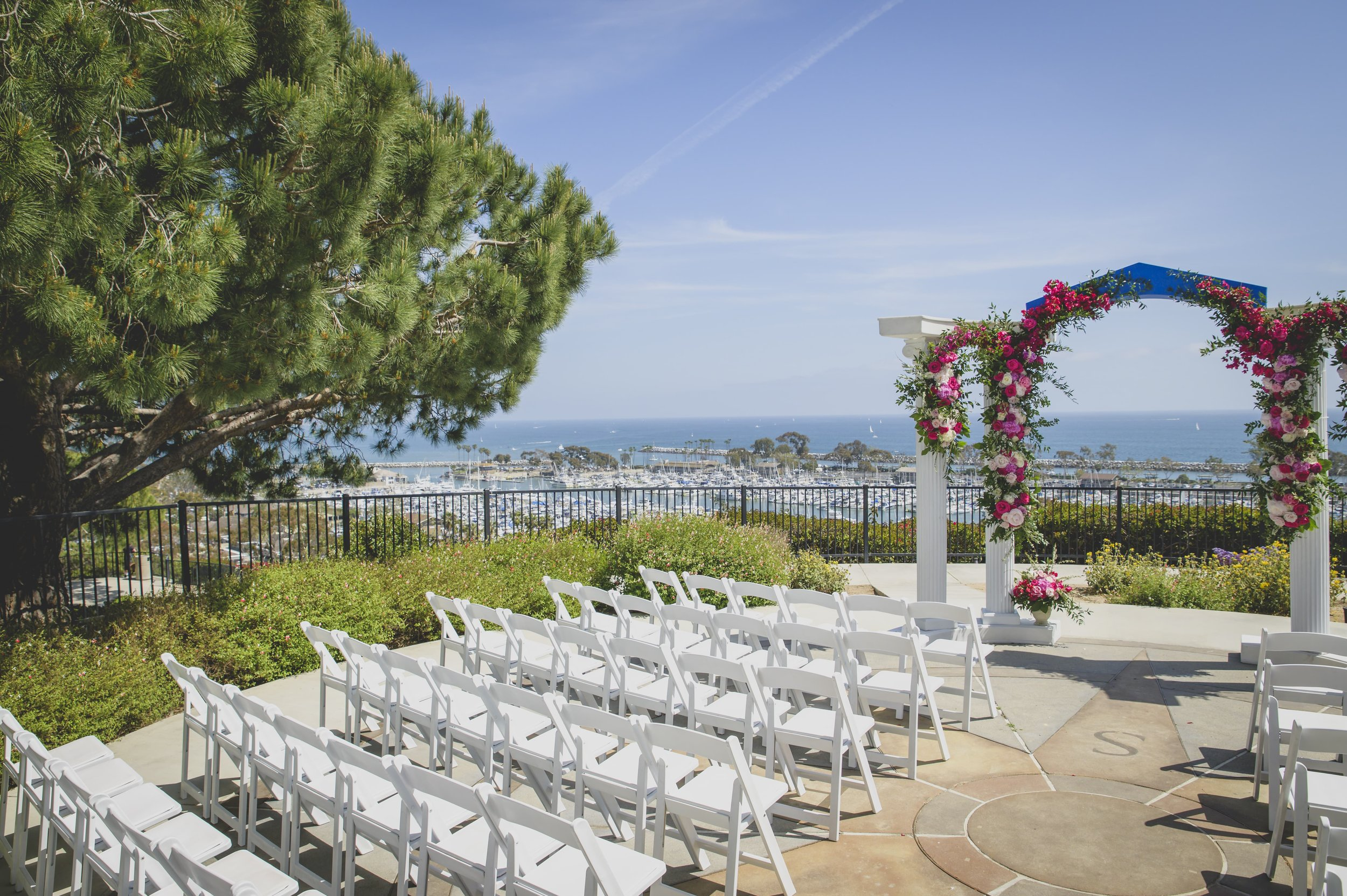 Wedding Photography Packages - Heritage Park, Dana Point, CA - Ceremony location with white flowered arches and the ocean in the background