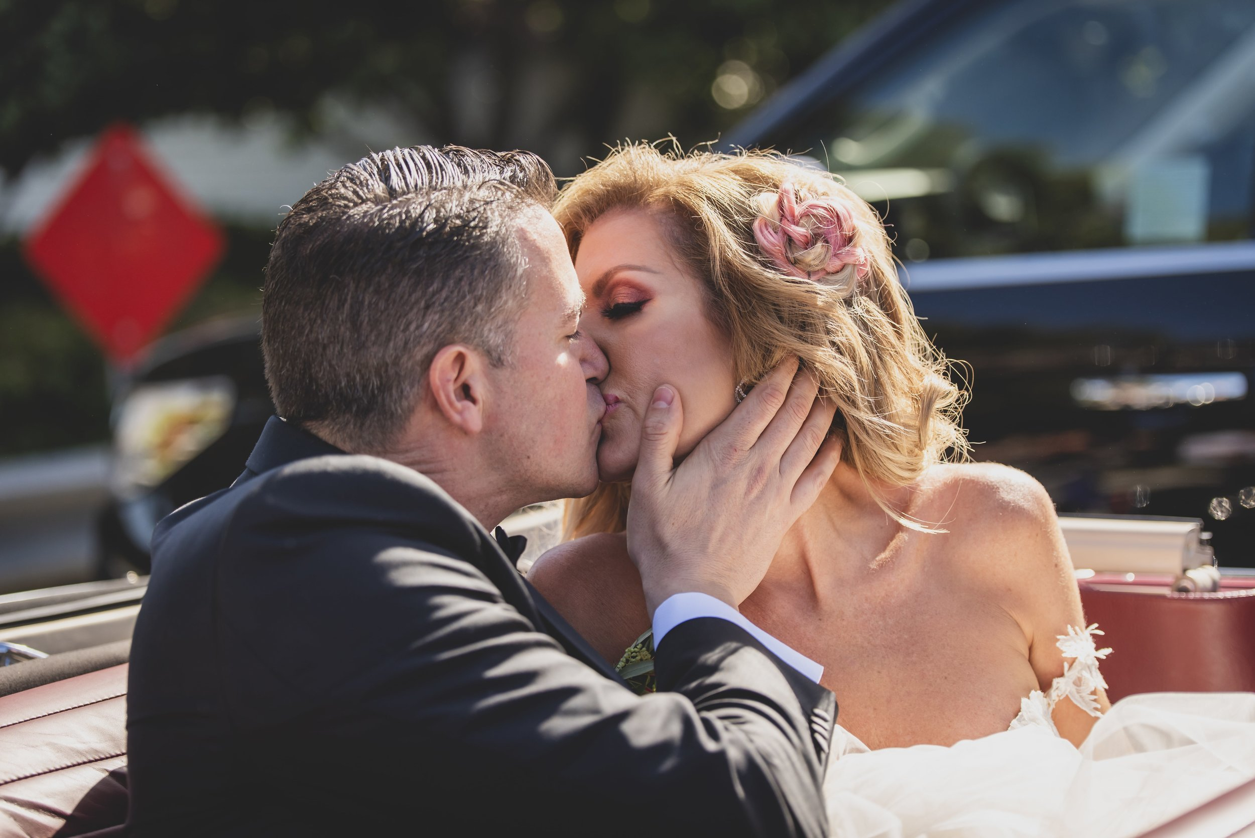 Wedding Photography Packages - Heritage Park, Dana Point, CA -Groom kissing the bride in their red getaway car.