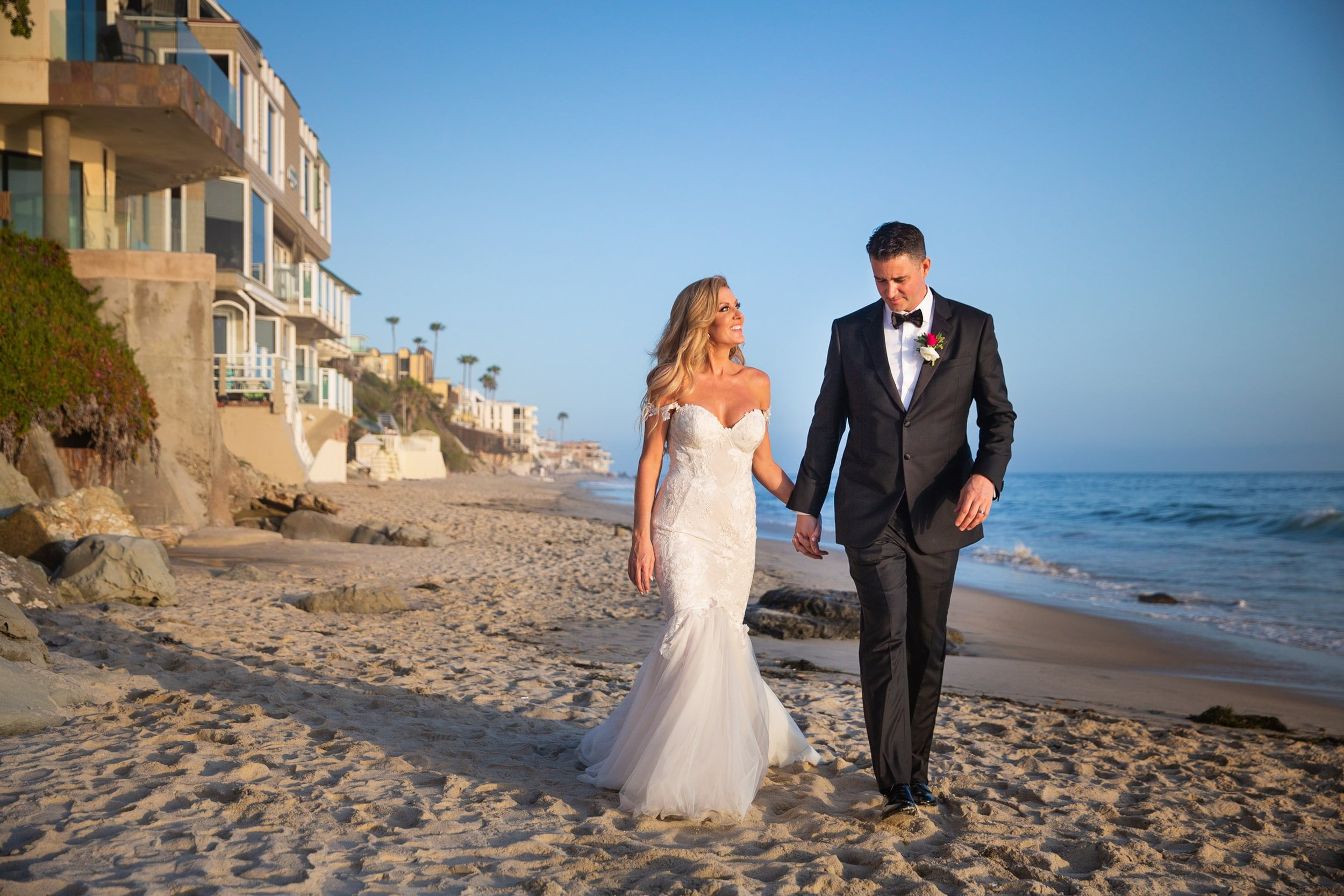 Wedding Photography Packages - Heritage Park, Dana Point, CA - The bride and groom walking hand in hand through the sand with the ocean in the background.