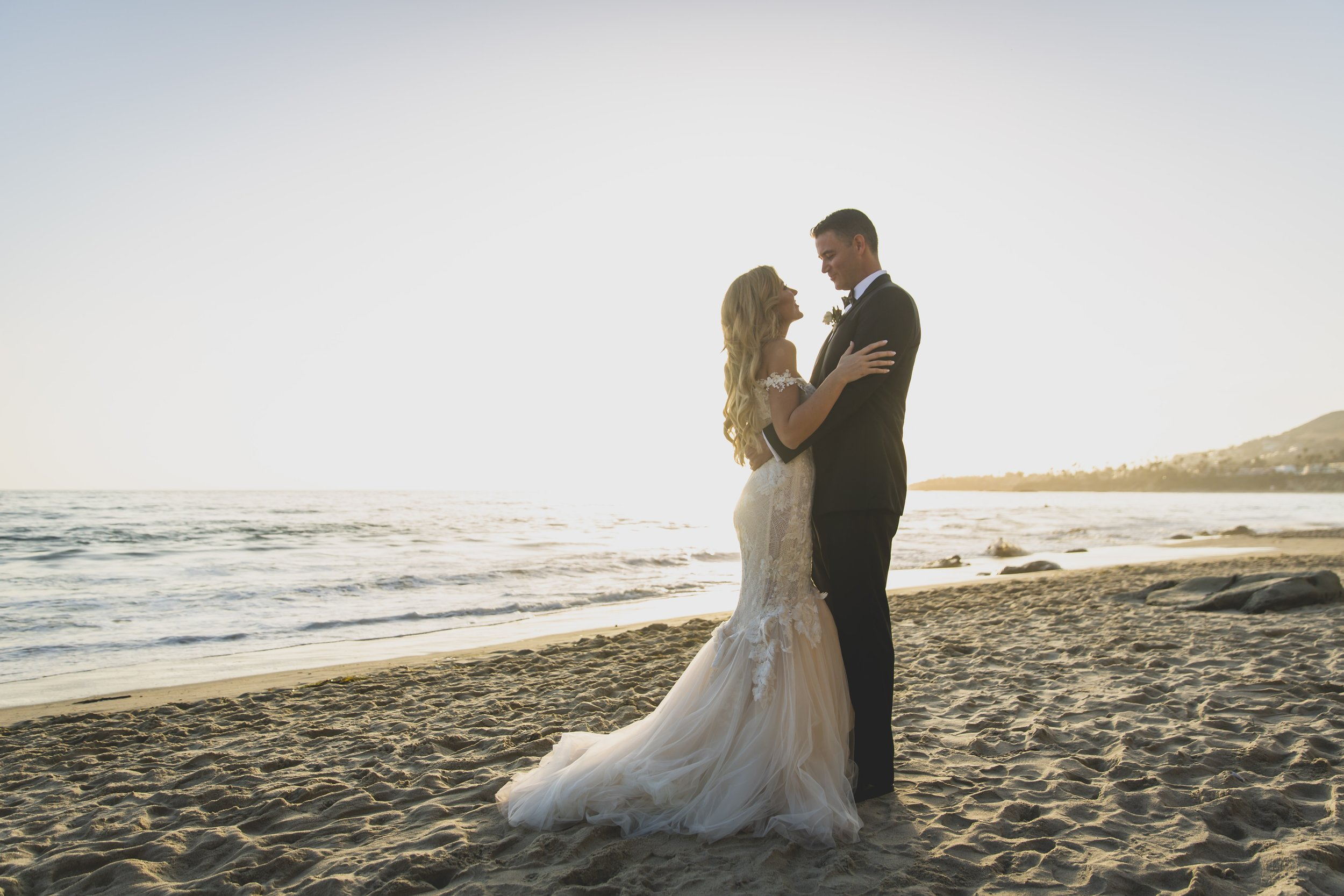 Wedding Photography Packages - Heritage Park, Dana Point, CA - Bride and groom embracing on the beach with the sun high in the sky as they stare into one another's eyes.