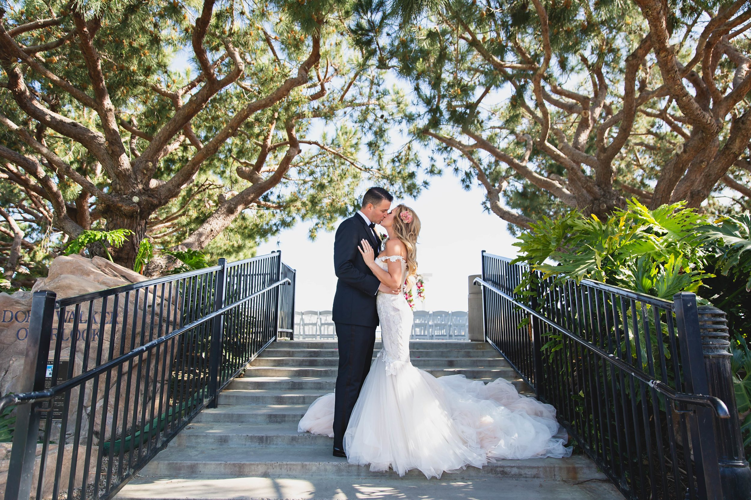 Wedding Photography Packages - Heritage Park, Dana Point, CA - Bride and groom kissing on a steep set of stairs leading to their ceremony location.
