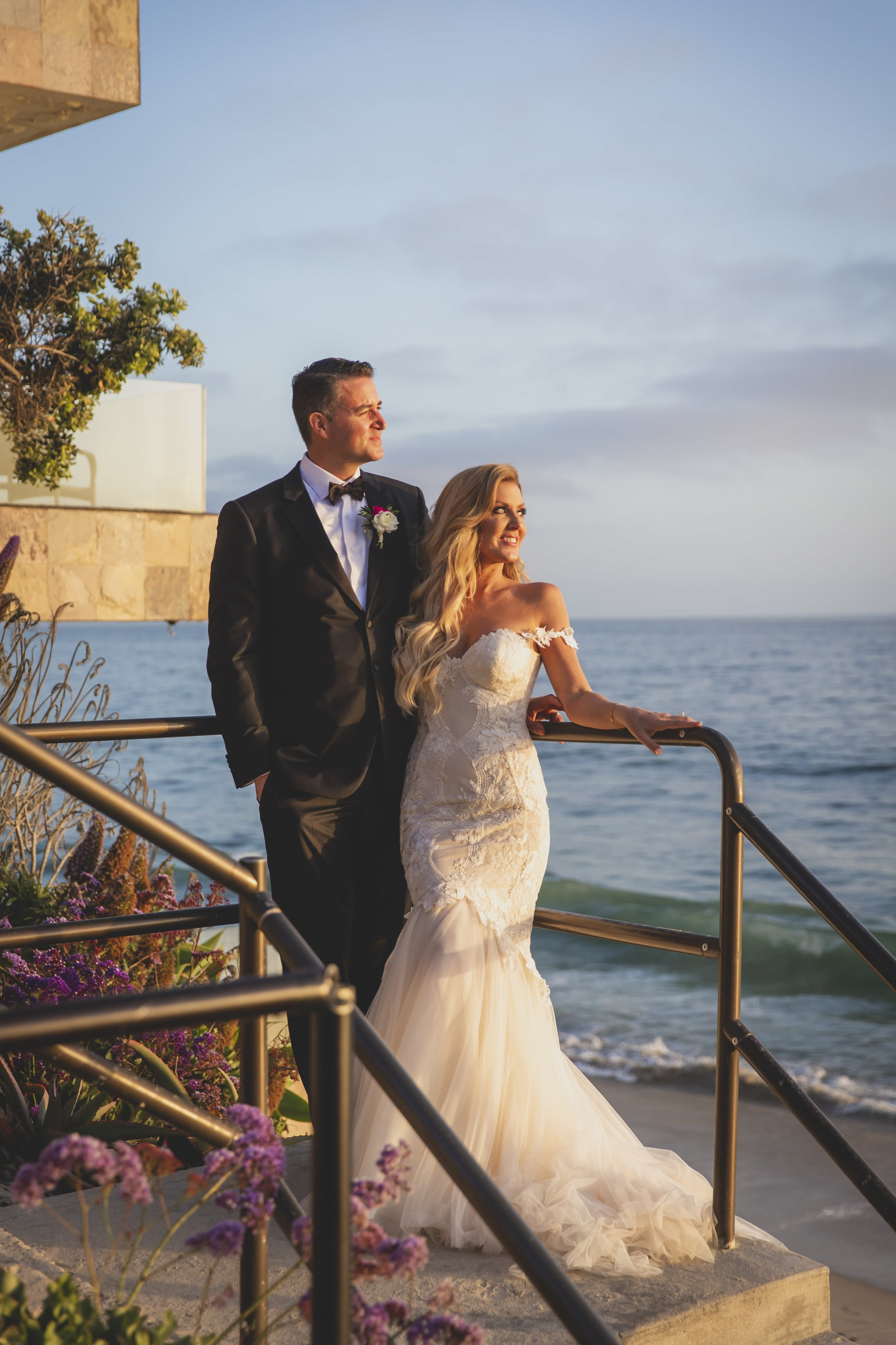 Wedding Photography Packages - Heritage Park, Dana Point, CA - Bride and groom standing at the top of a set of stairs, staring into the ocean as the sun begins to set.