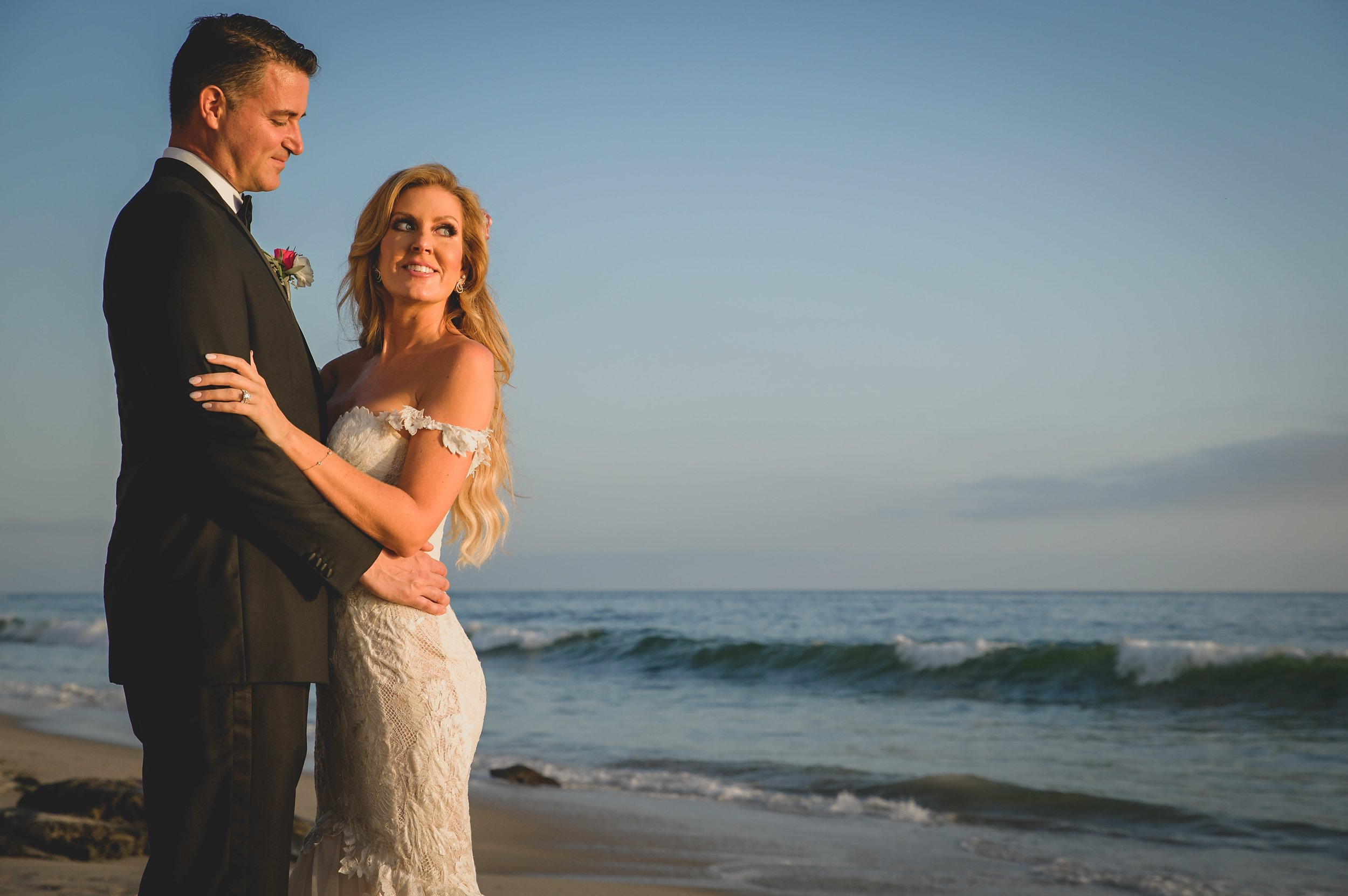 Wedding Photography Packages - Heritage Park, Dana Point, CA - Bride and groom standing on the beach with the ocean in the background and the sun beginning to set.