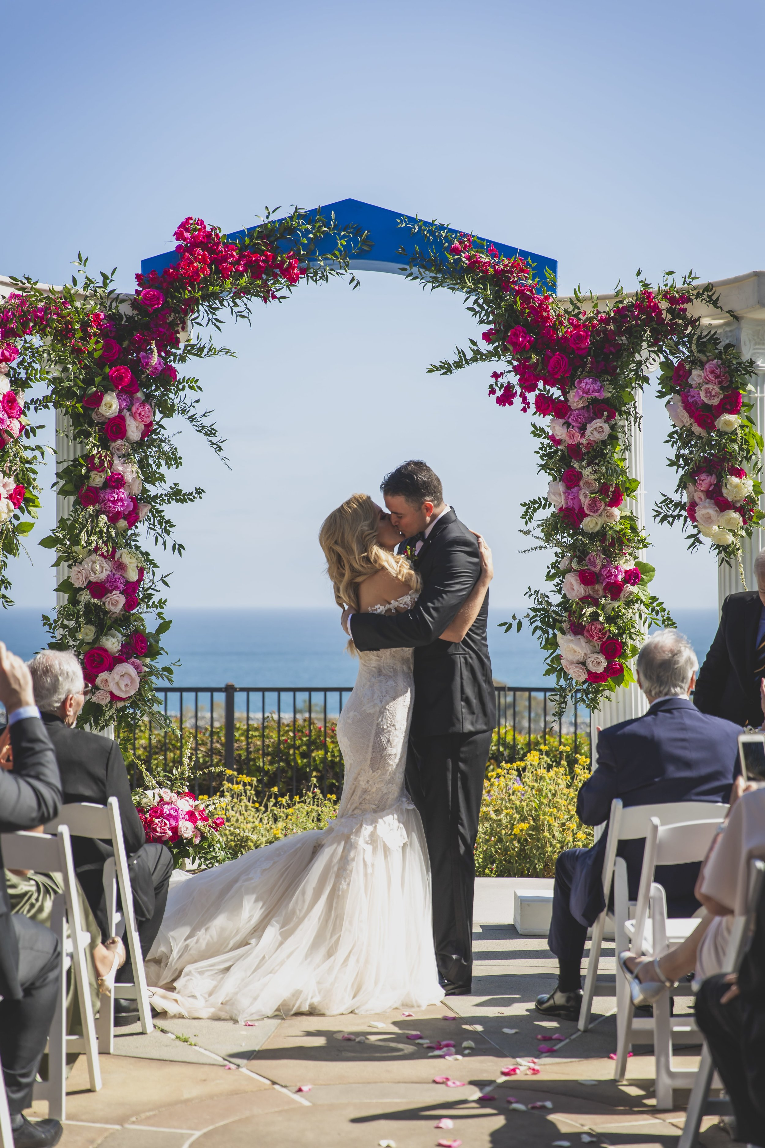 Wedding Photography Packages - Heritage Park, Dana Point, CA - Groom kissing the bride to seal their marriage during the wedding ceremony.