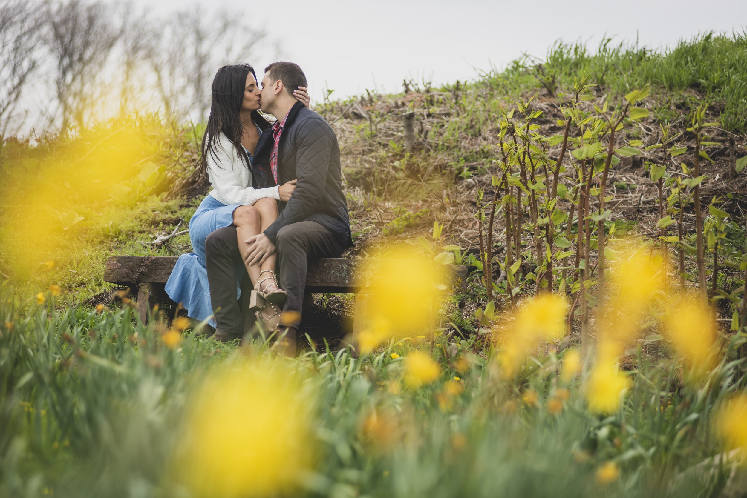 Engagement Photography Services - Castle Hill Lighthouse, Newport, RI - Couple kissing on a bench surrounded by flowers