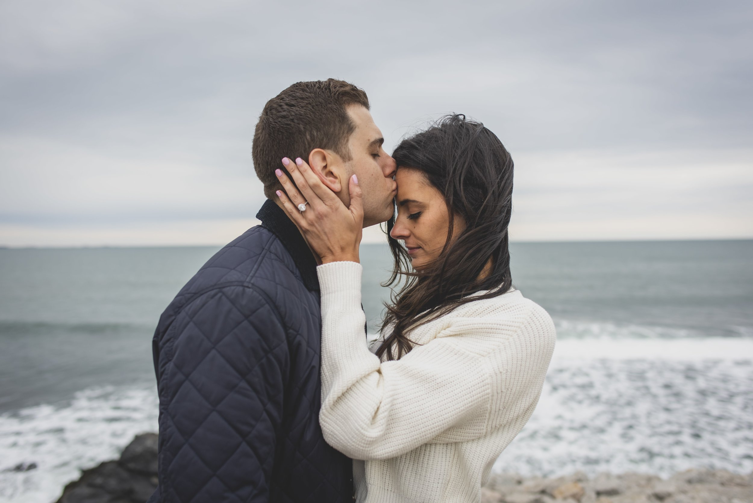 Engagement Photography Services - Castle Hill Lighthouse, Newport, RI - Future groom kissing future bride on the forehead.