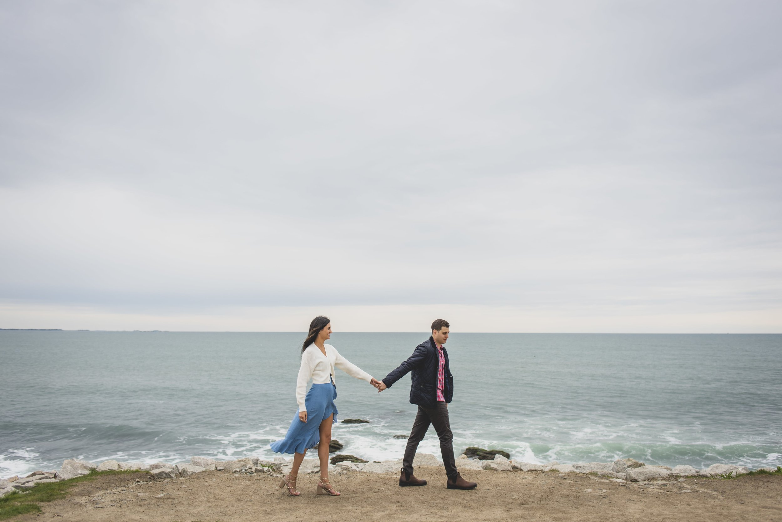 Engagement Photography Services - Castle Hill Lighthouse, Newport, RI - Future groom leading future bride by the hand along the shoreline with the ocean in the background.
