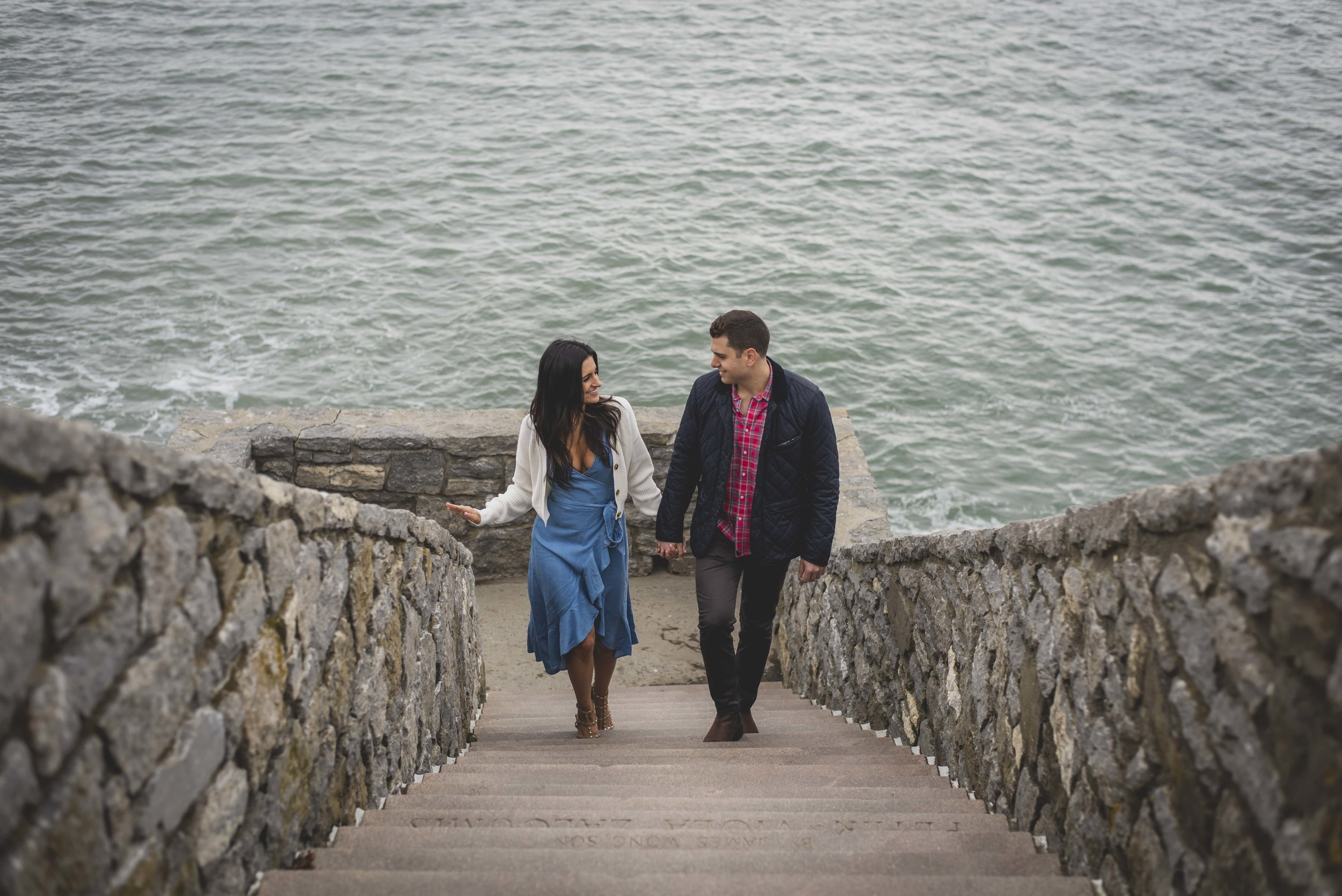 Engagement Photography Services - Castle Hill Lighthouse, Newport, RI - Couple walking hand in hand up stone stairs with the ocean behind them.