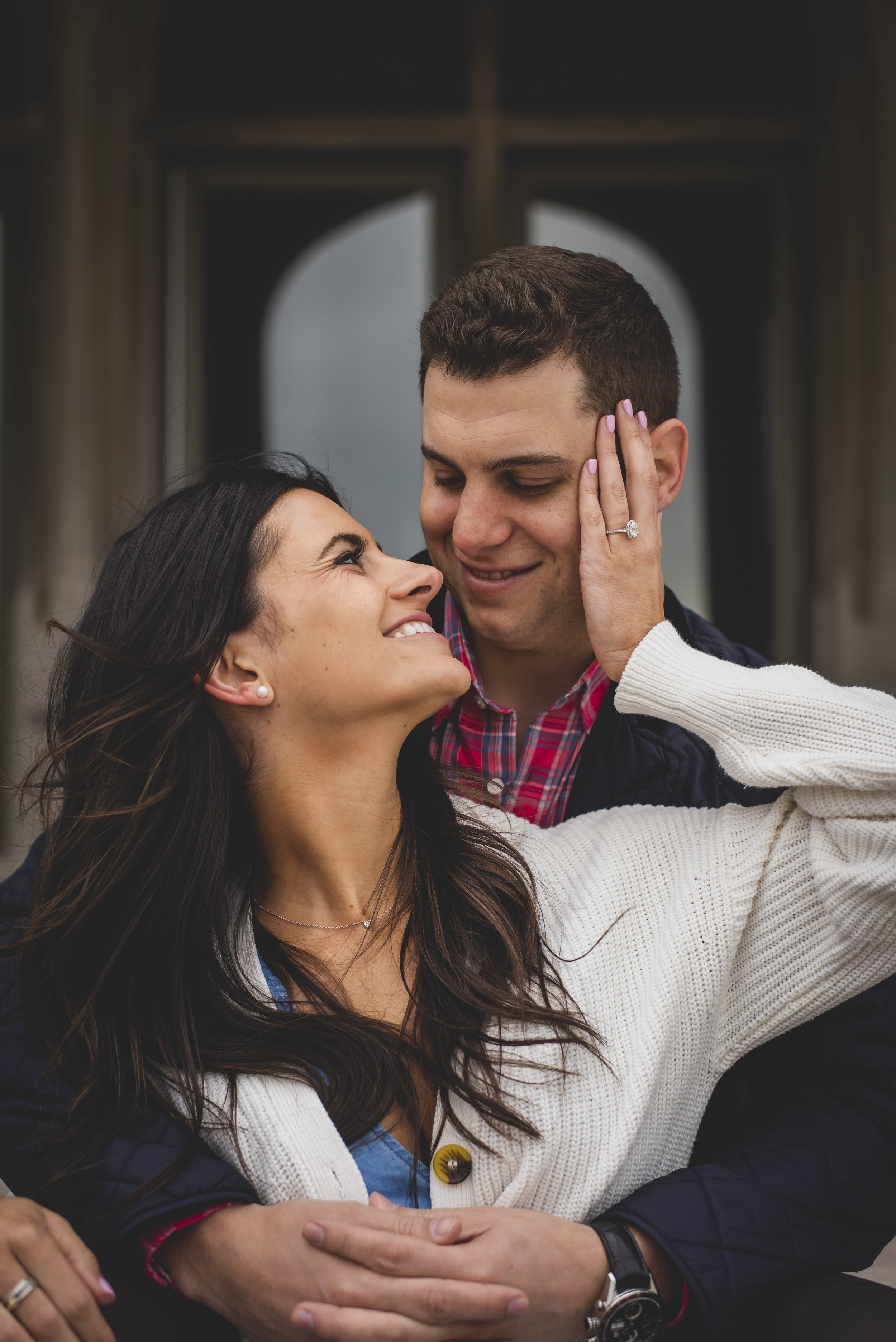 Engagement Photography Services - Castle Hill Lighthouse, Newport, RI - Future bride looking over her shoulder into her future husbands eyes as she sits in front of him.
