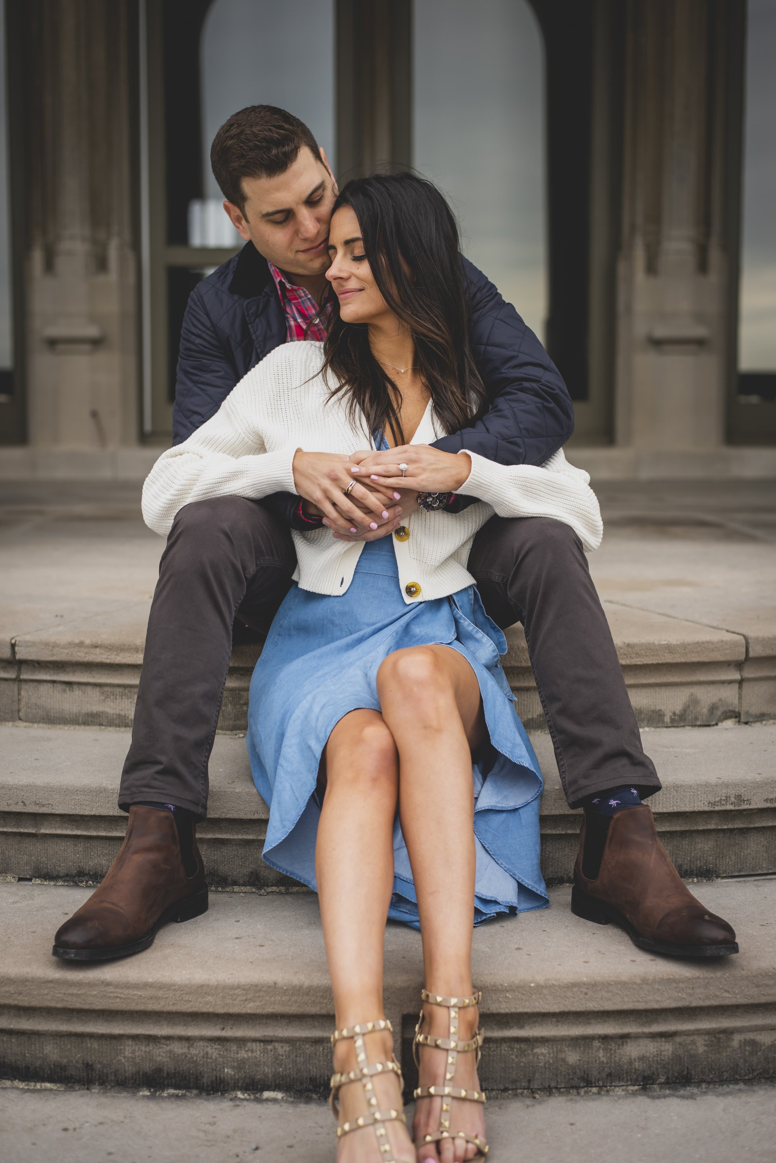 Engagement Photography Services - Castle Hill Lighthouse, Newport, RI - Couple sitting together on stone stairs as the future groom holds his future bride.