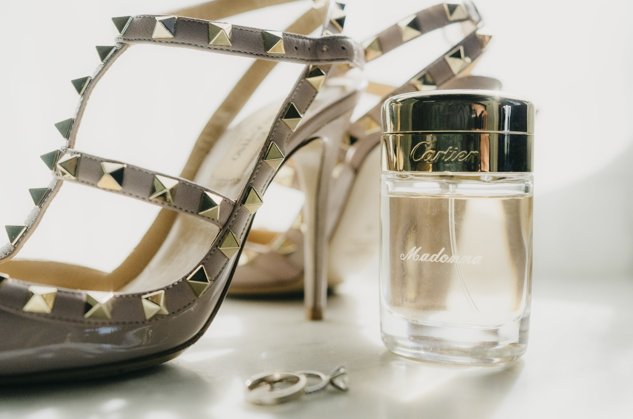 Wedding Photography - Something Old, Something New, Something Borrowed, Something Blue - Wedding bands photographed in front of a bottle of perfume and gold high heels.