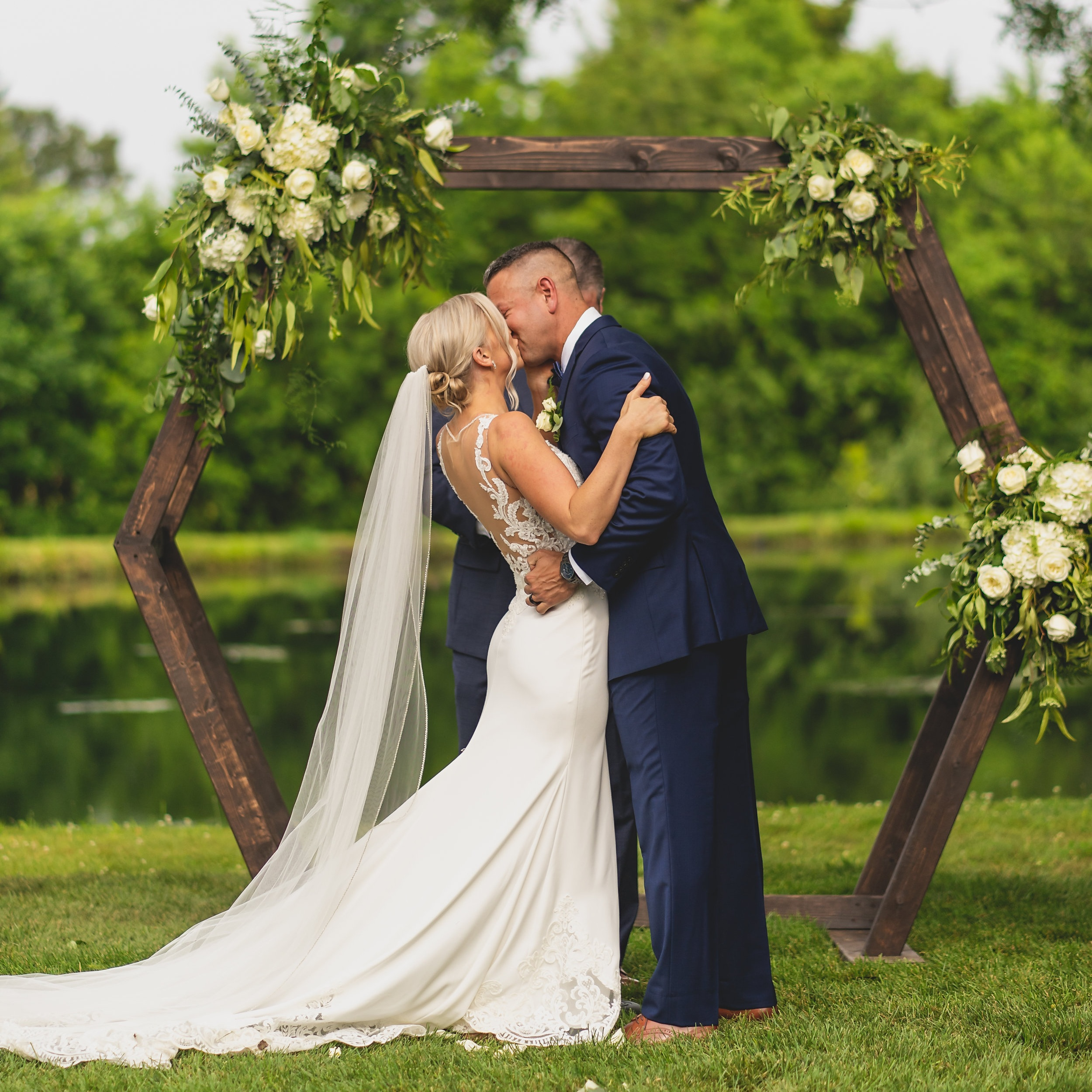 Rustic themed wedding - Bride and groom kiss in front of geometric wooden arches.