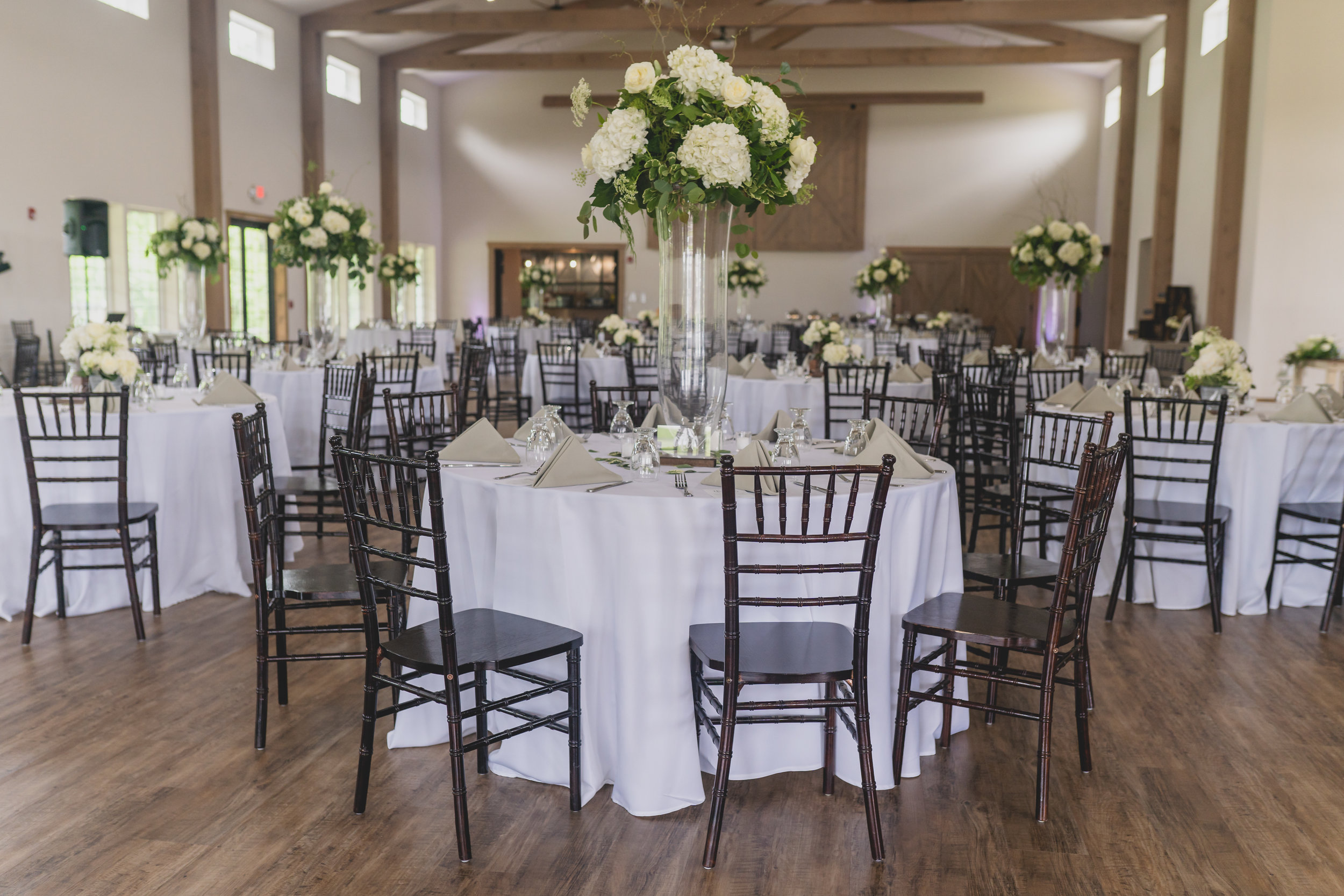 Rustic themed wedding - Reception hall featuring large white floral centerpieces and neutral color tones.