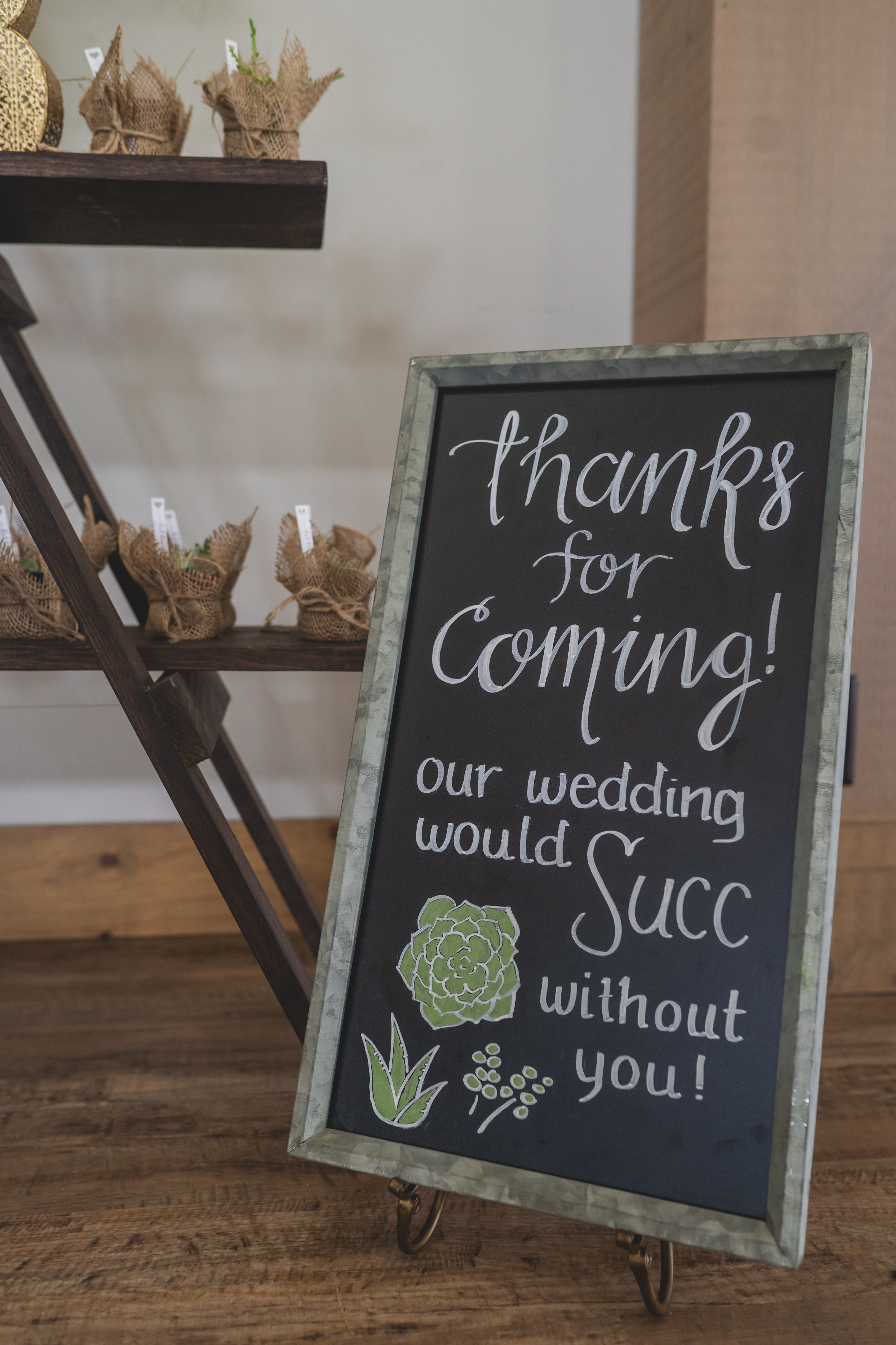 Rustic themed wedding - A table of wedding favors holding succulent plants wrapped in burlap.