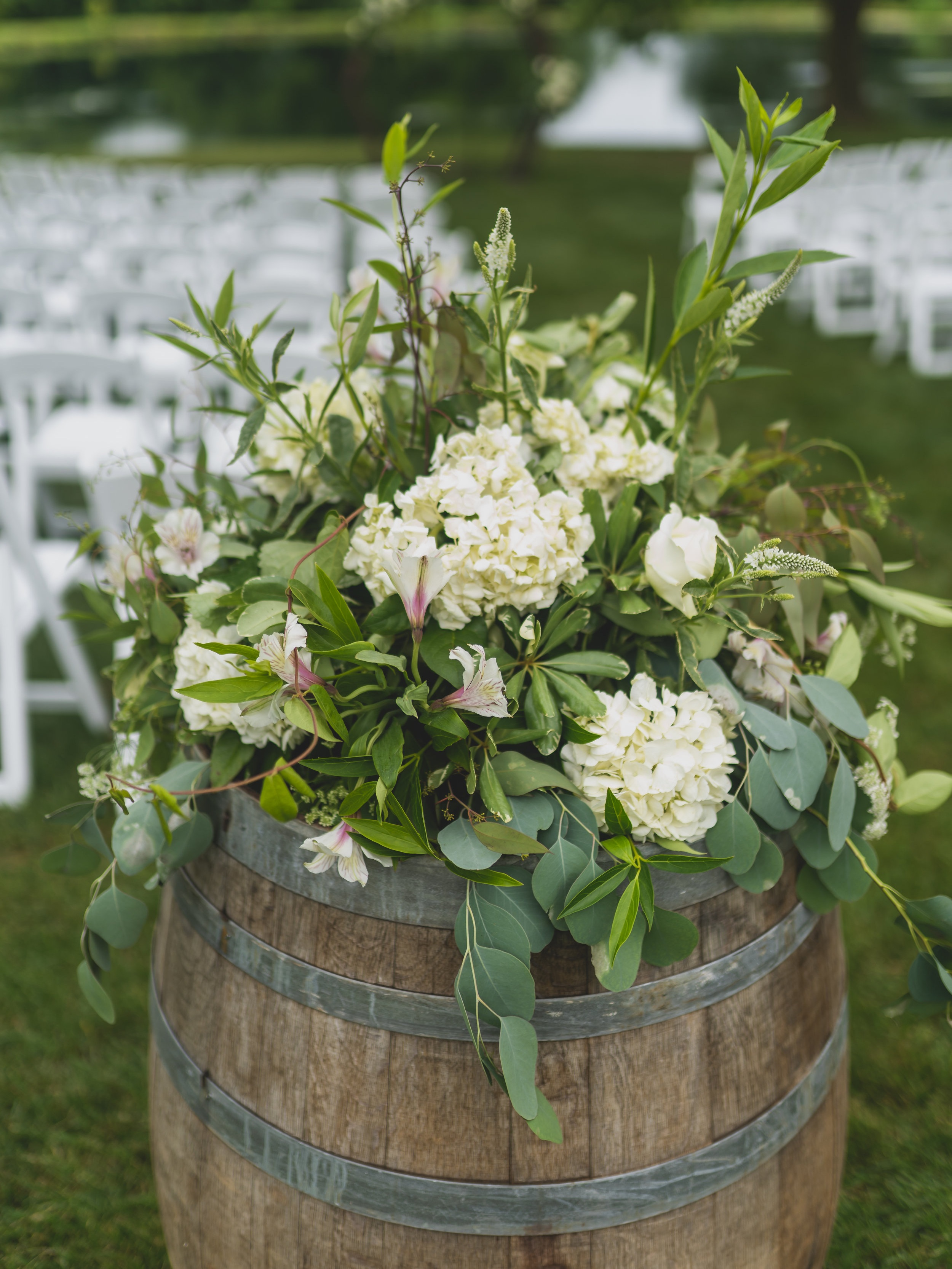 Rustic themed wedding - White flowers in a wooden barrel.