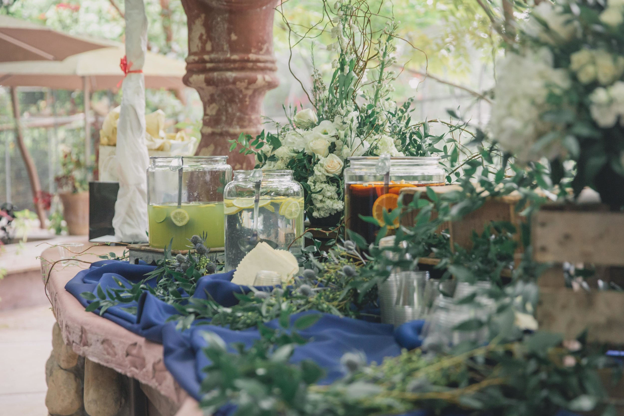 Ways to keep guests cool at your warm-weather wedding - A table decorated with flowers and greenery at an outdoor wedding ceremony stocked with refreshments.