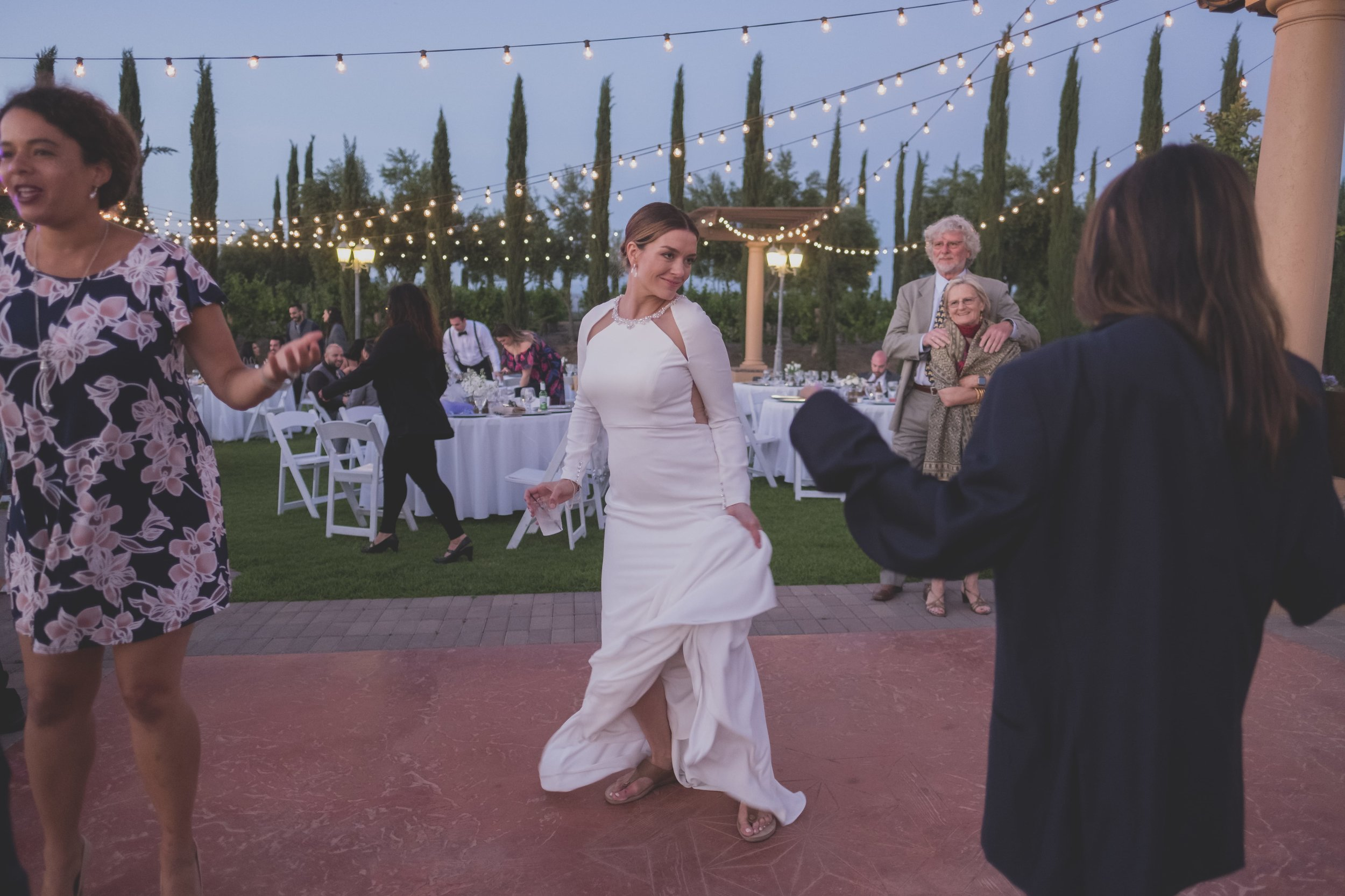 Ways to keep guests cool at your warm-weather wedding - Bride at her outdoor reception dancing solo under a darkening sky.