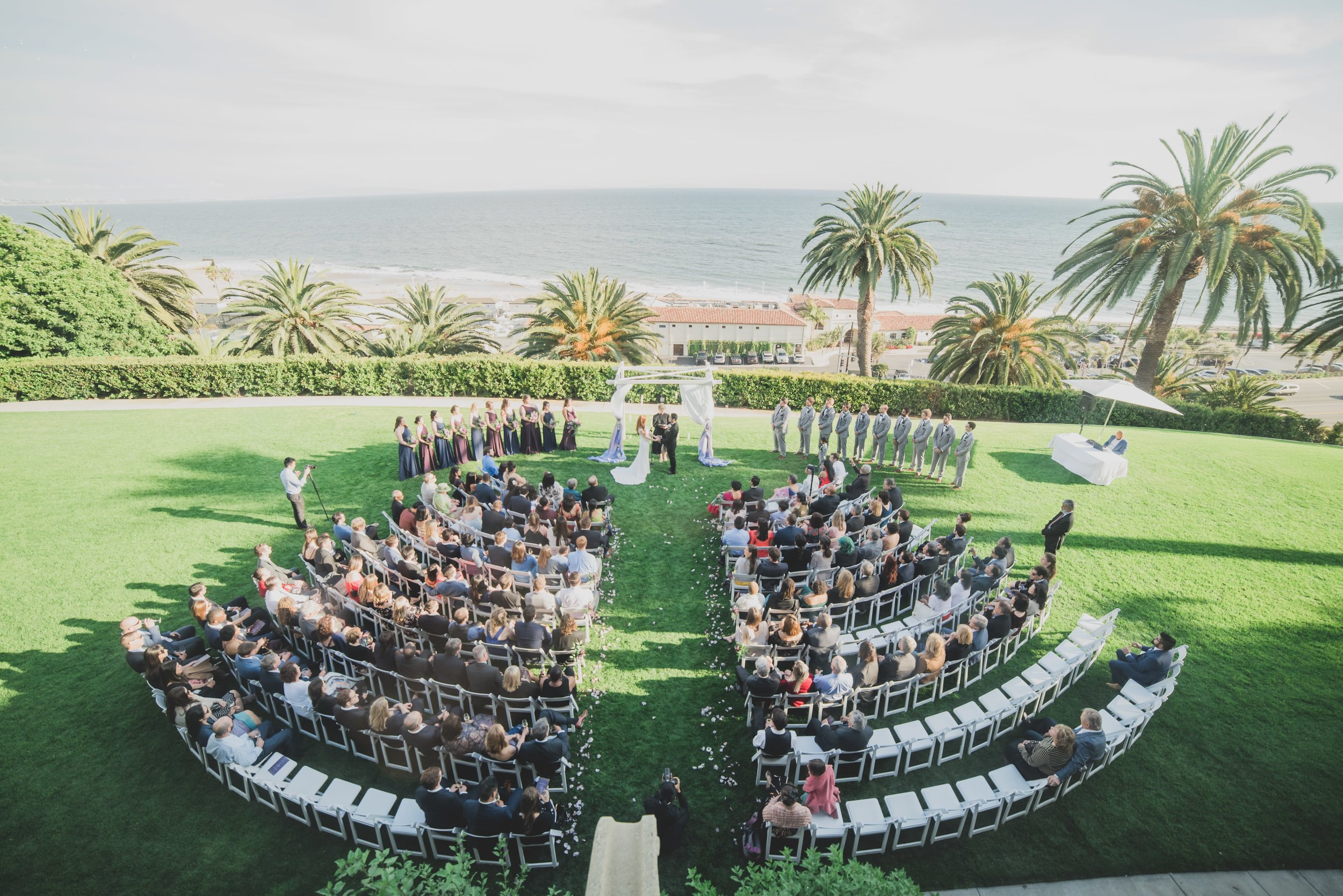 Ways to keep guests cool at your warm-weather wedding - Aerial shot of a beachfront wedding ceremony.