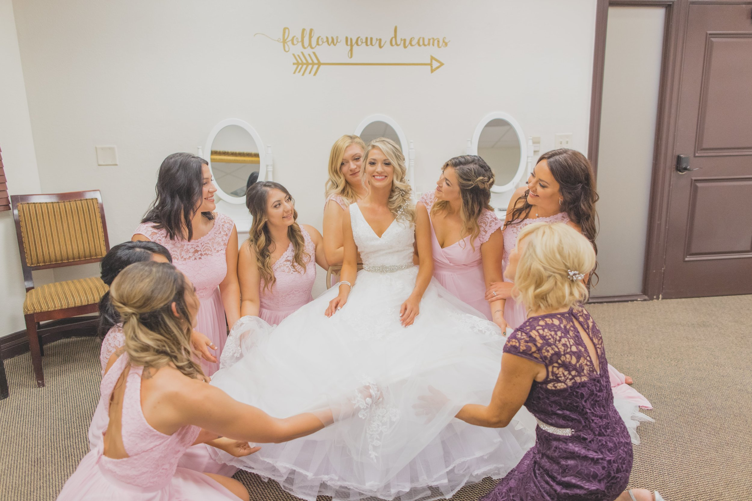 wedding dress shopping 101 - tips for finding the perfect dress - Bride in her wedding dress surrounded by her bridesmaids.