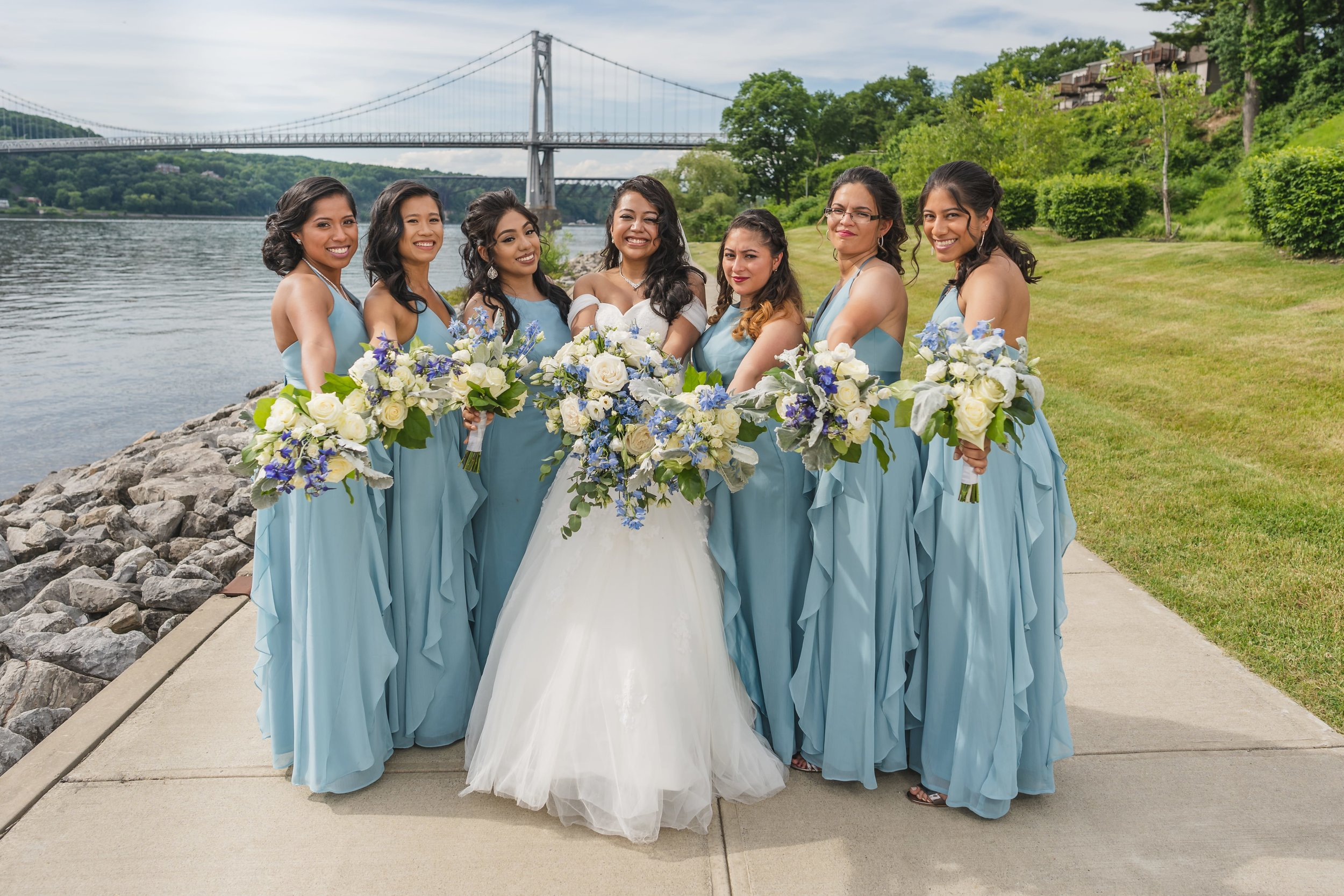 How to choose bridesmaid dresses everyone will love - Bride with her bridesmaids holding flowers.