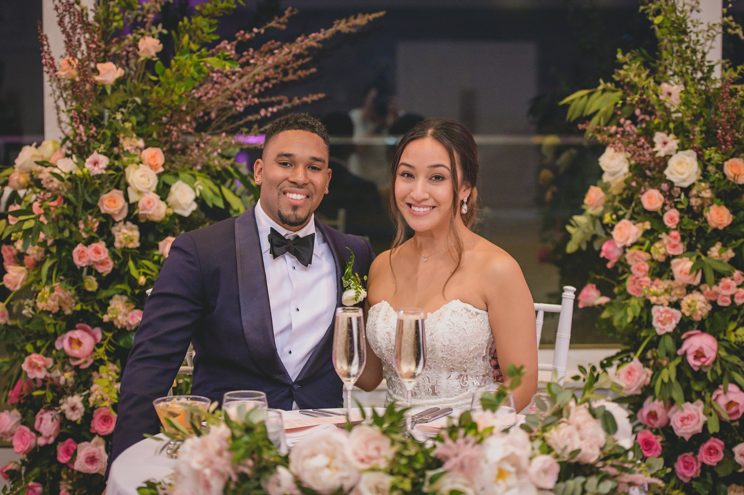 Helpful tips for choosing a wedding photographer - Bride and groom sitting at the reception table surrounded by flowers.