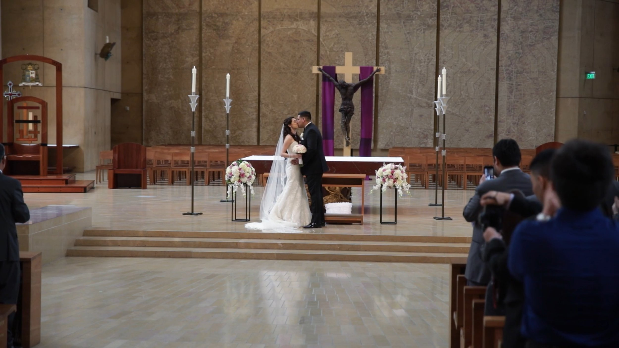 Wedding videography los angeles, CA - Cathedral of Our Lady of the Angels - Newly married couple kissing at the altar.