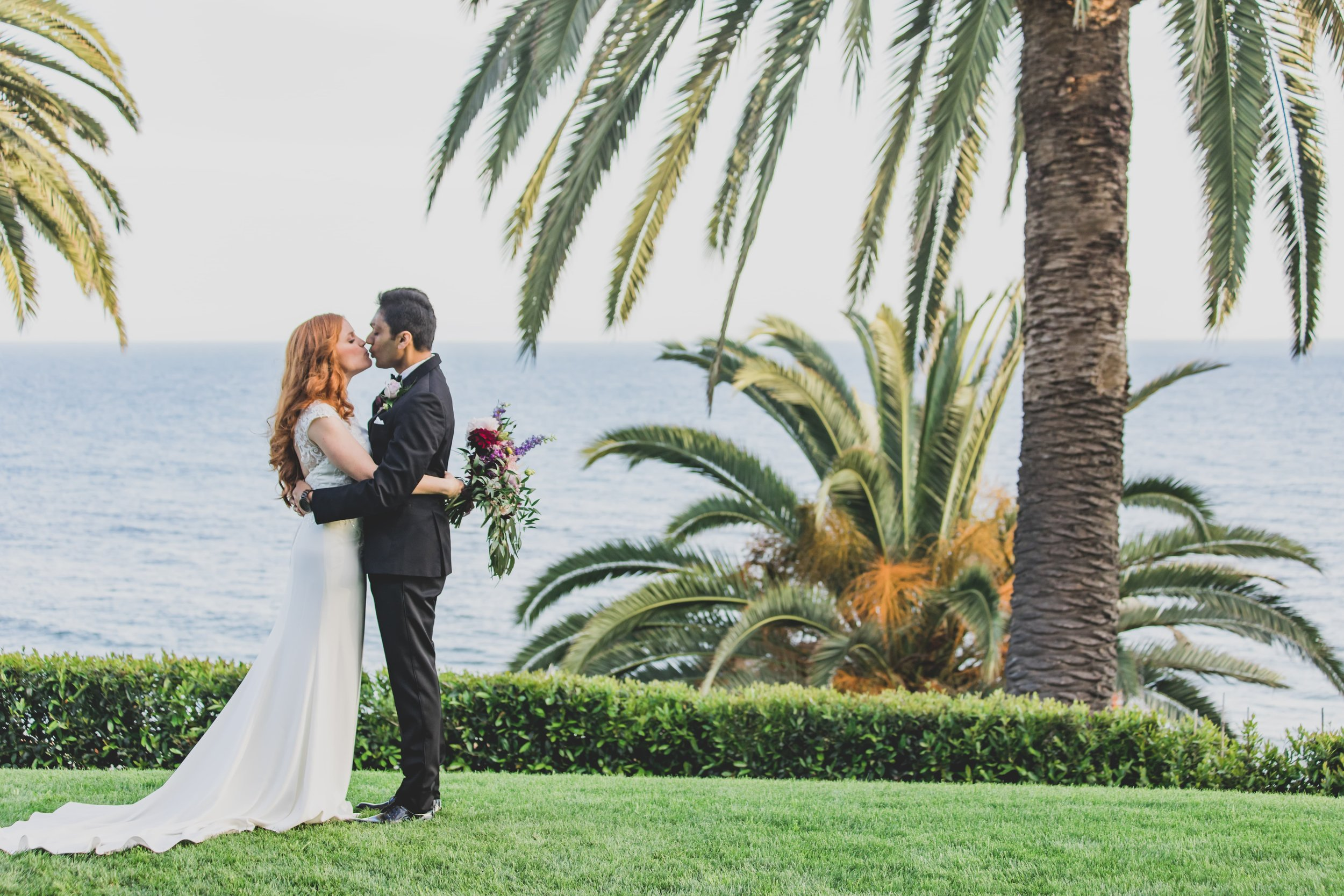 Wedding Photography - Pacific Palisades, CA - Bel Air Bay Club - Bride and groom kissing on a grassy enclosure, with palm trees in the background and the ocean behind them.