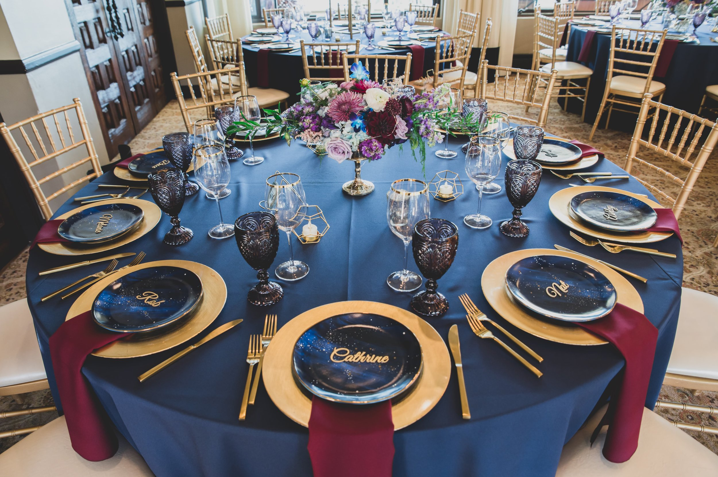 Wedding Photography - Pacific Palisades, CA - Bel Air Bay Club - A guest table in the reception hall decorated with navy blue, gold, and a colorful floral centerpiece.