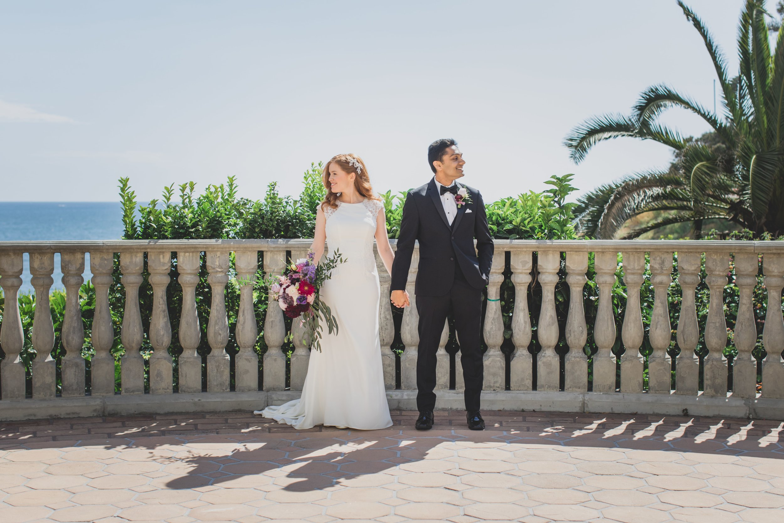 Wedding Photography - Pacific Palisades, CA - Bel Air Bay Club - Bride and groom standing on a sunlit balcony overlooking the ocean.