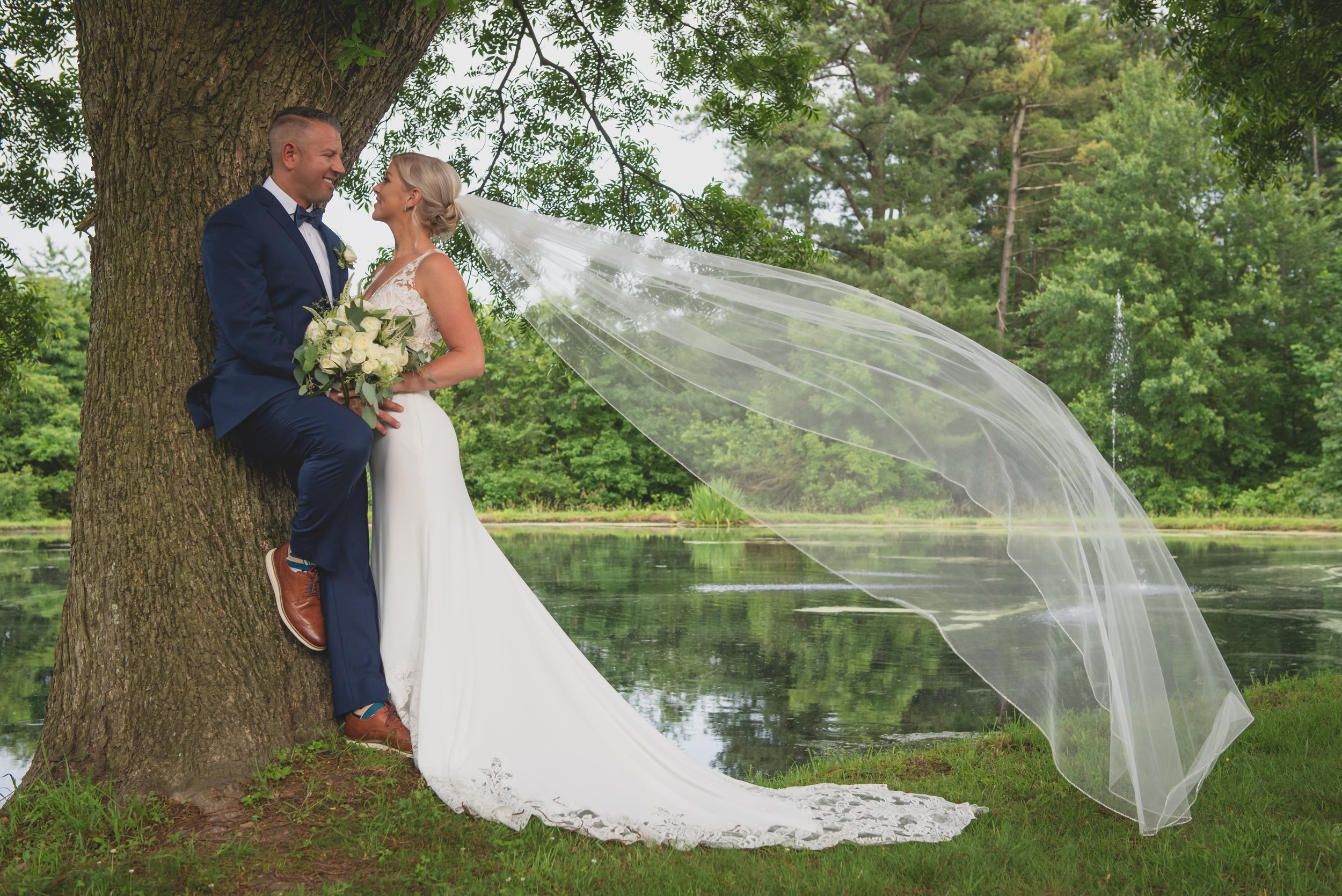 Summer Wedding Trends 2019 - Groom leaning against a tree in front of a pond with his bride in his arms.
