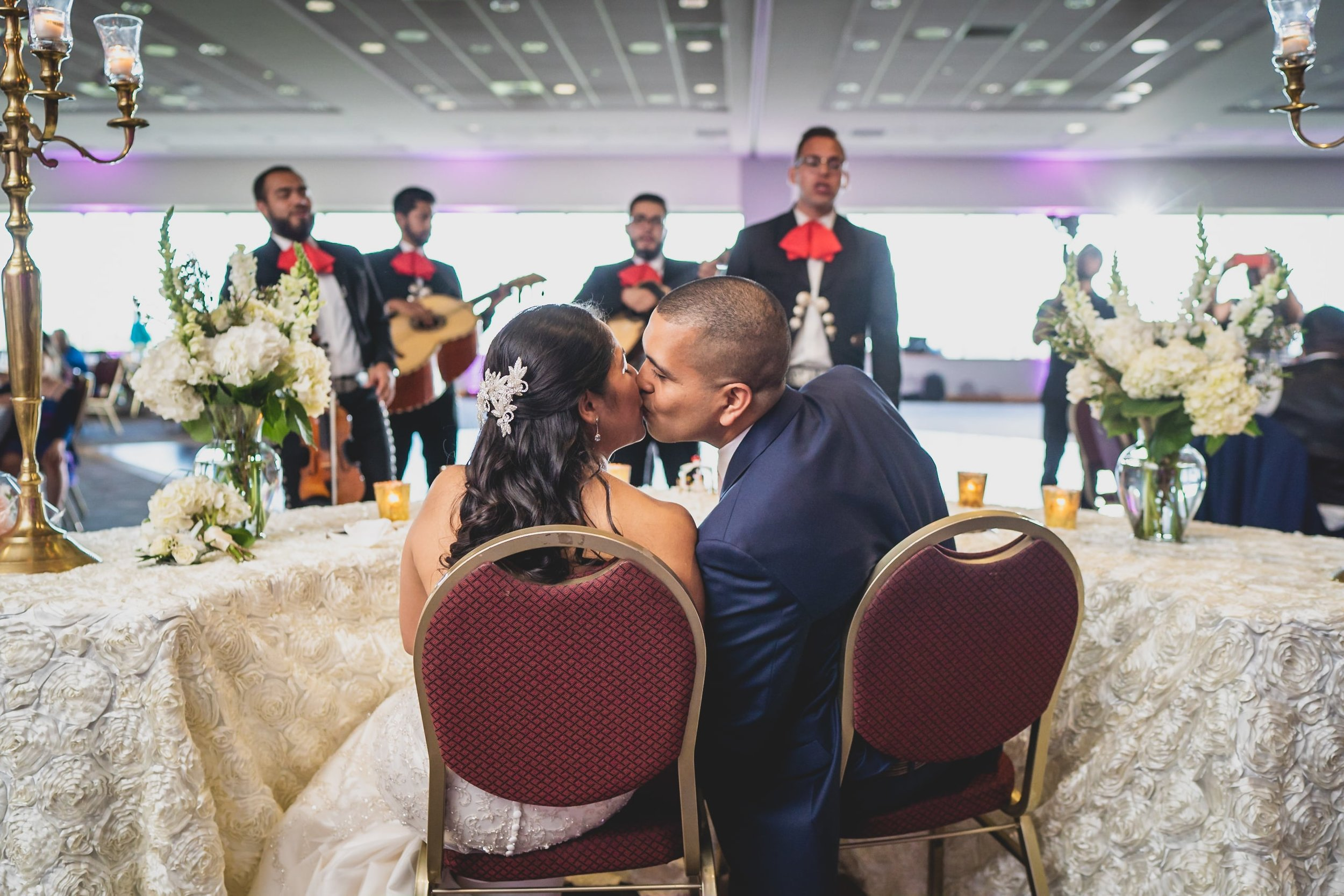 Wedding Videography - San Antonio, TX - Bride and groom kissing as a performers serenade them at the head table.