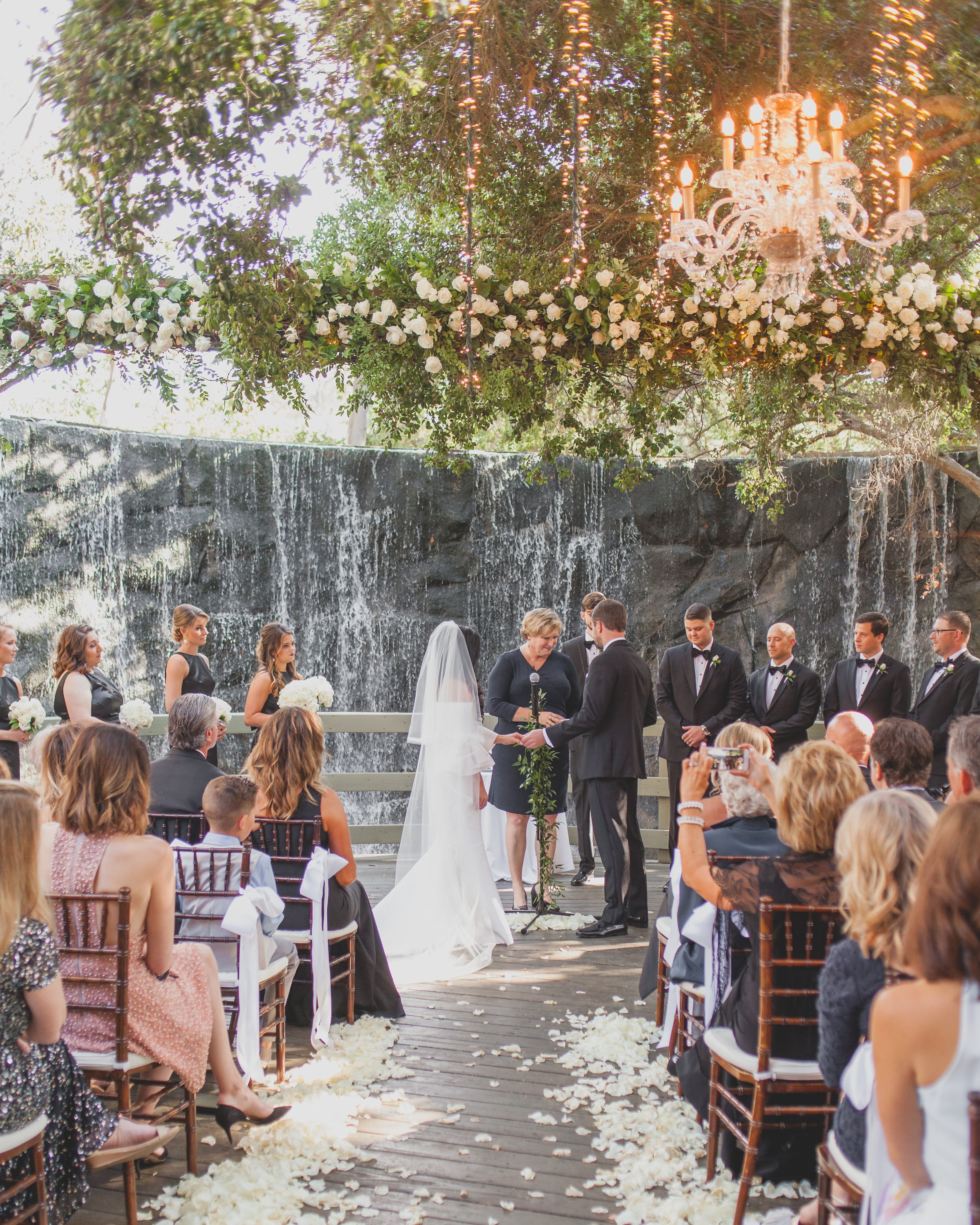 Garden Wedding Theme Feature - Wedding ceremony in front of a natural stone waterfall and stunning chandeliers draping from lush greenery.