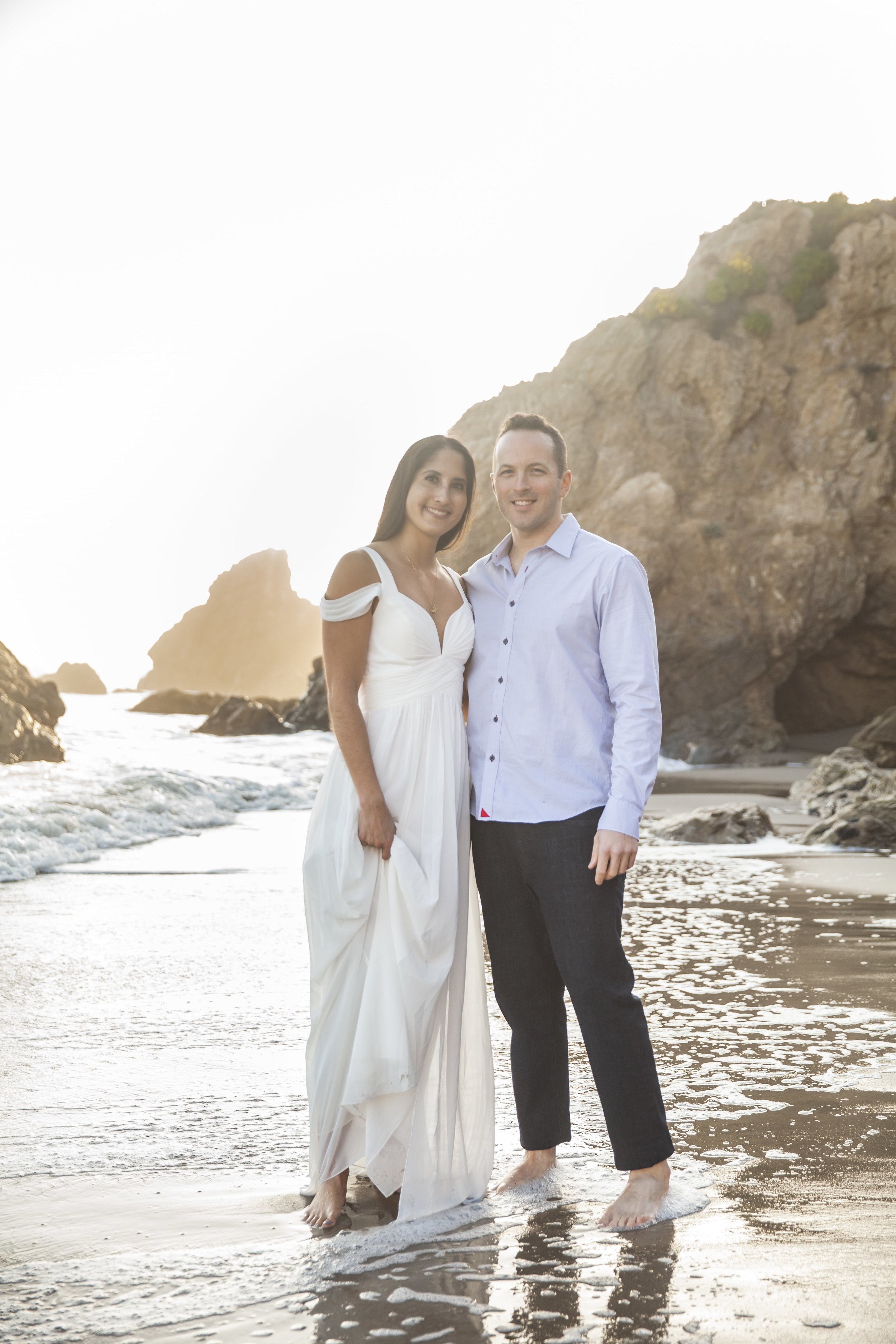 California Engagement Photography - Engaged couple standing barefoot on the coast with their feet in the ocean.
