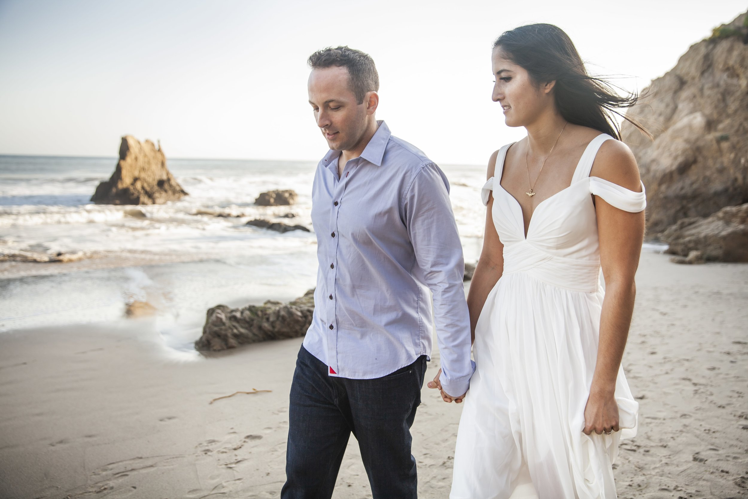 California Engagement Photography - Engaged couple walking hand in hand along the beach front.
