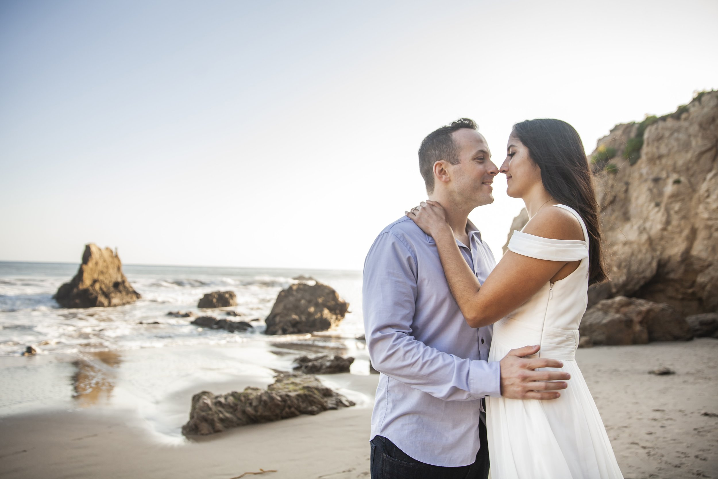 California Engagement Photography - Engaged couple leaning in for a kiss with ocean waves crashing in the background.
