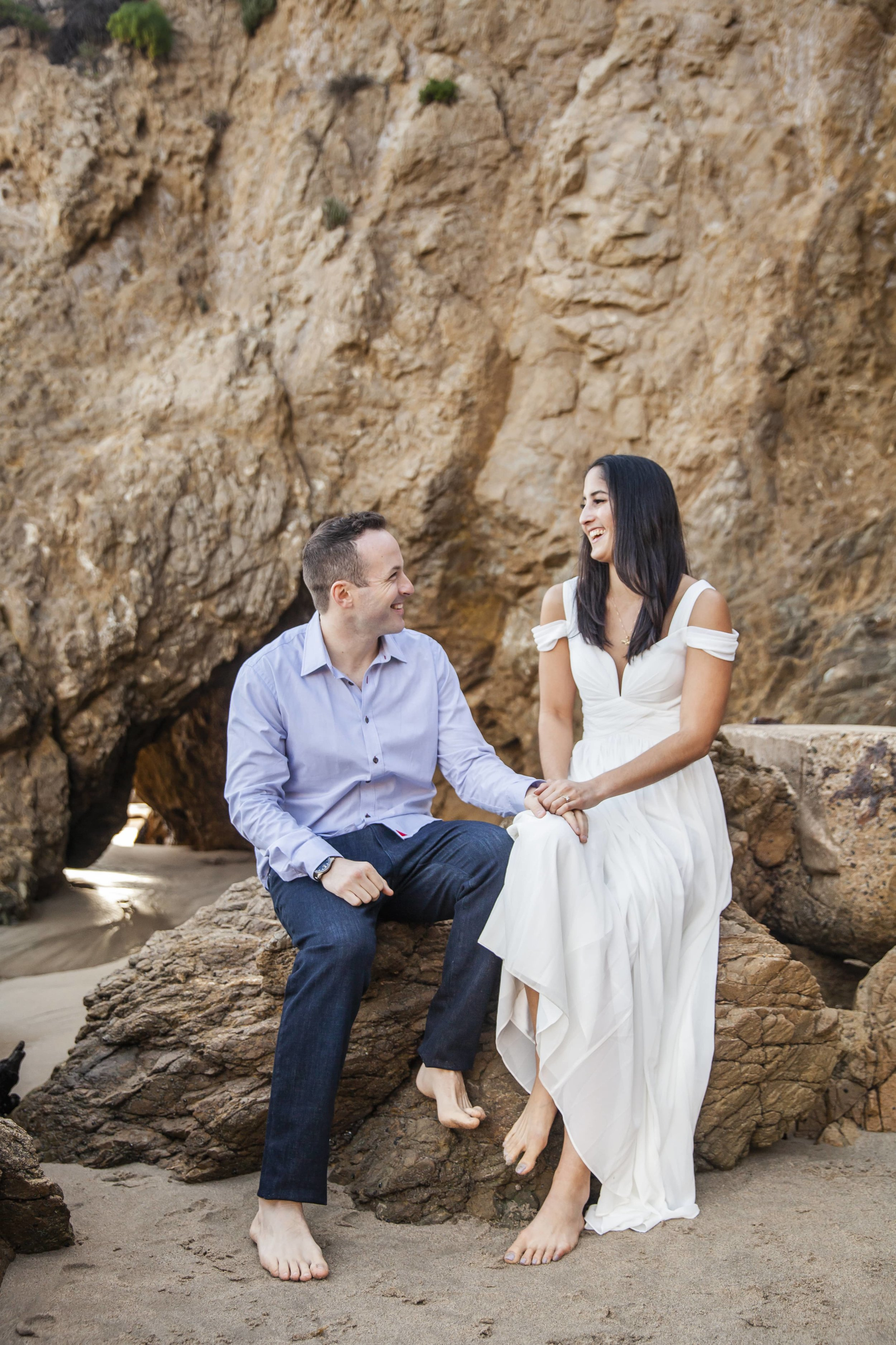 California Engagement Photography - Happy couple sitting on a rock laughing together.