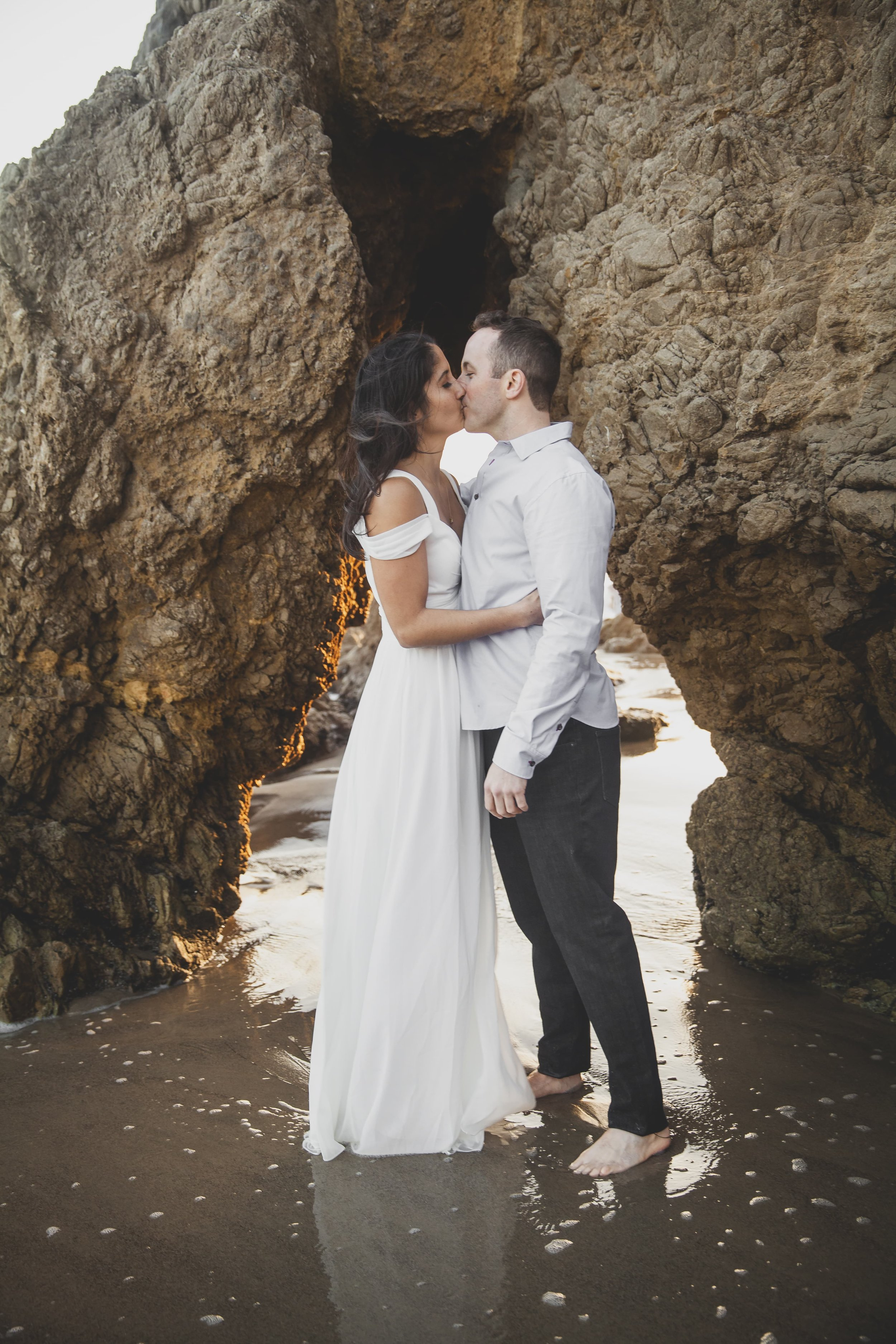 California Engagement Photography - Engaged couple kissing in the water while showered with rays of sunlight.