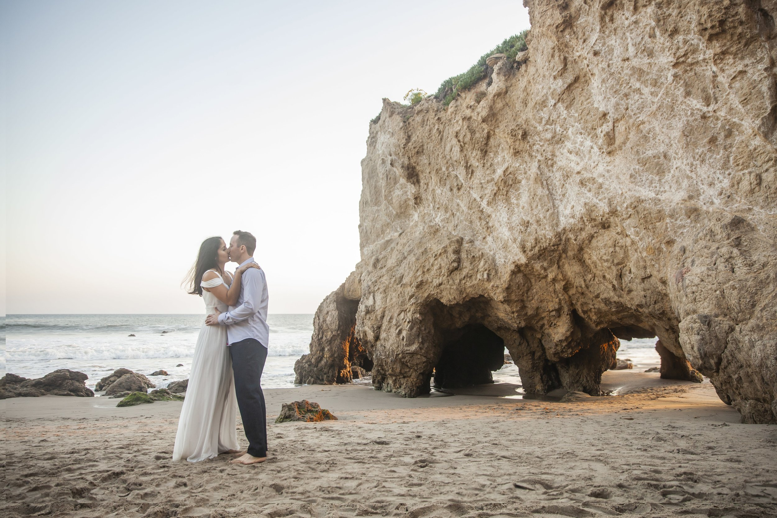 California Engagement Photography - Man and woman kissing in front of a large rock on a California beach.