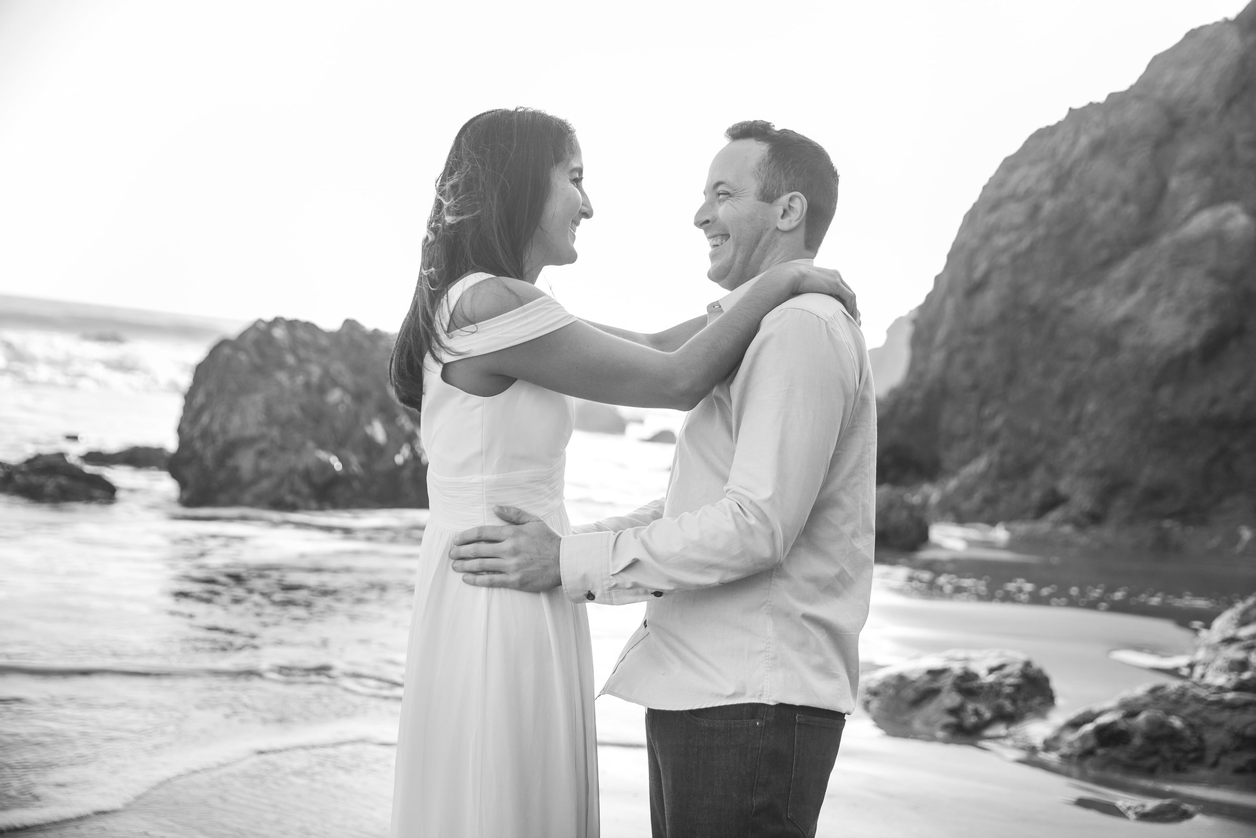 California Engagement Photography - Black and white photo of an engaged couple laughing on the beach.