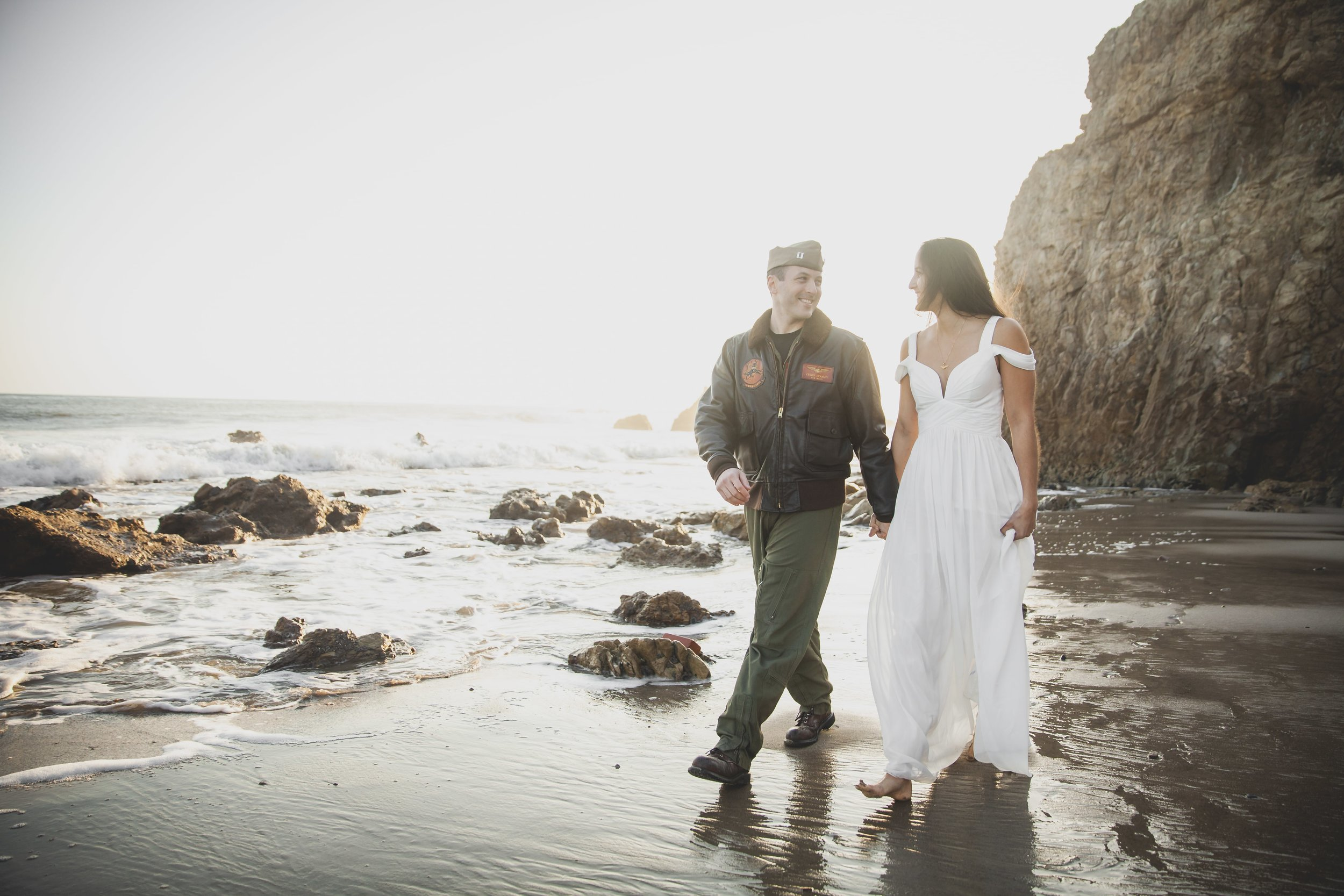 California Engagement Photography - Man in green military uniform walking with a woman in a white dress along the beach.