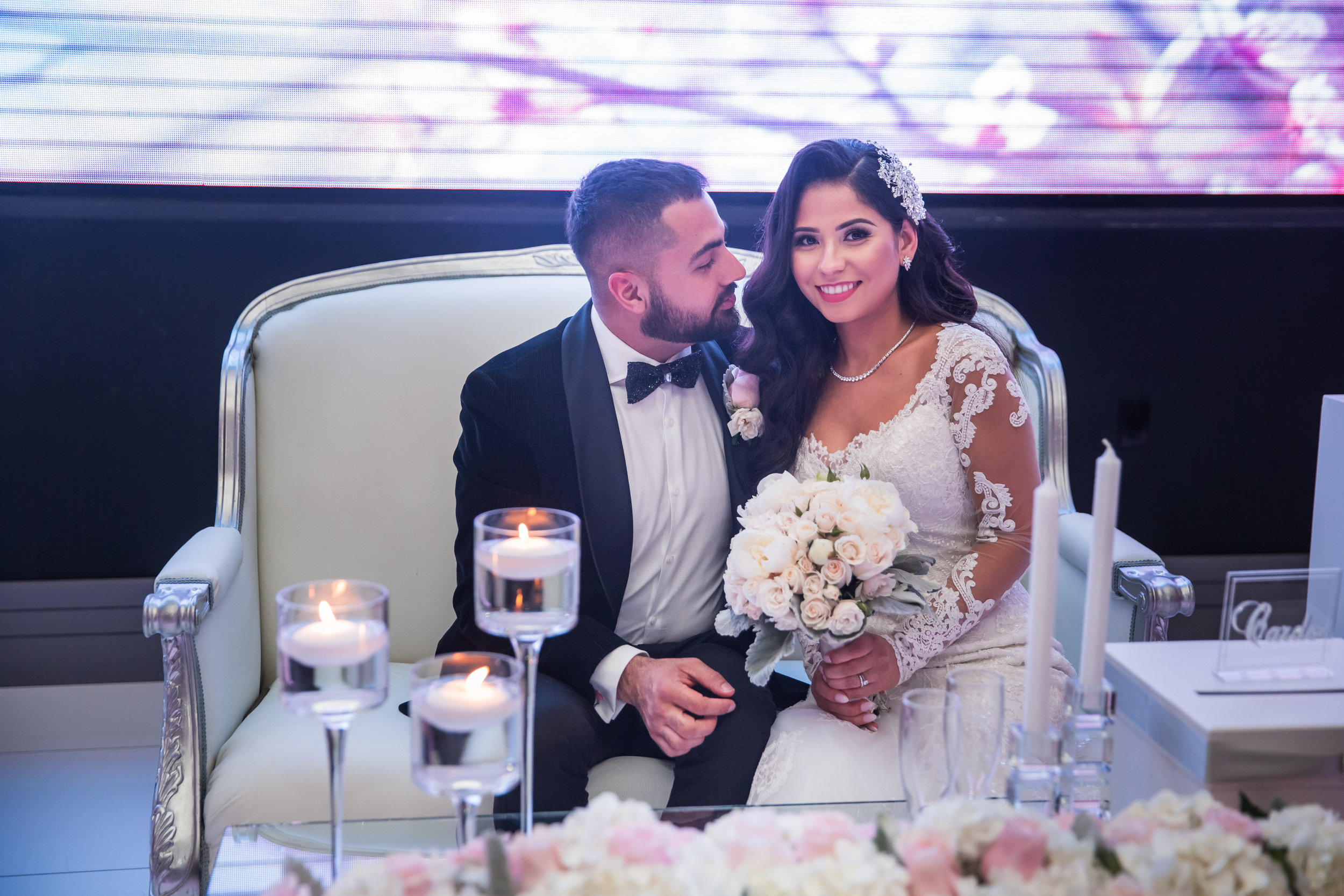 Romantic Wedding Theme Feature - Glendale, CA - Legacy Ballroom - Newlywed couple sitting together on a love seat in front a table decorated with flowers and candles.