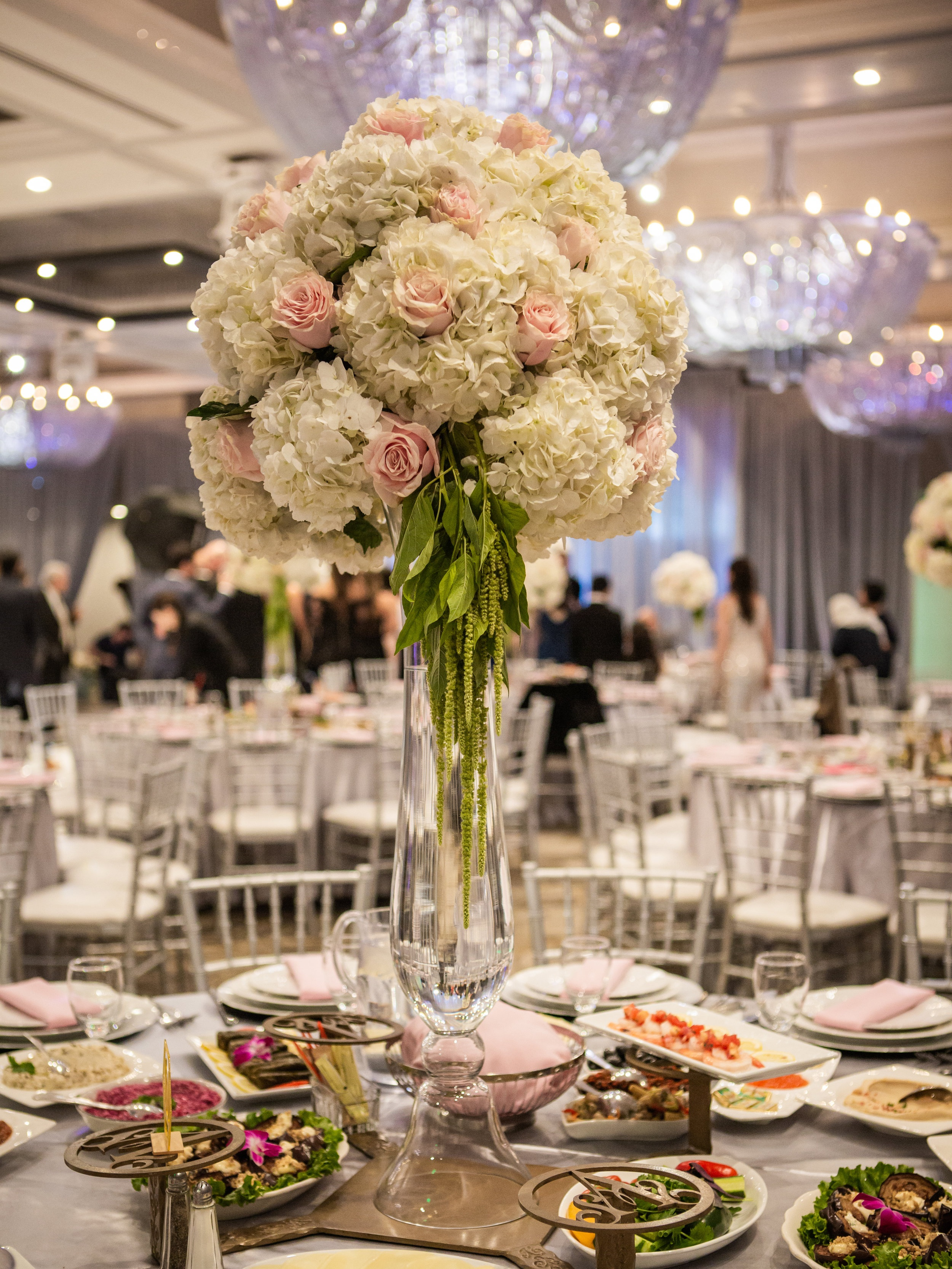 Romantic Wedding Theme Feature - Glendale, CA - Legacy Ballroom - A wedding reception table adorned with a large floral arrangement in a tall glass vase.
