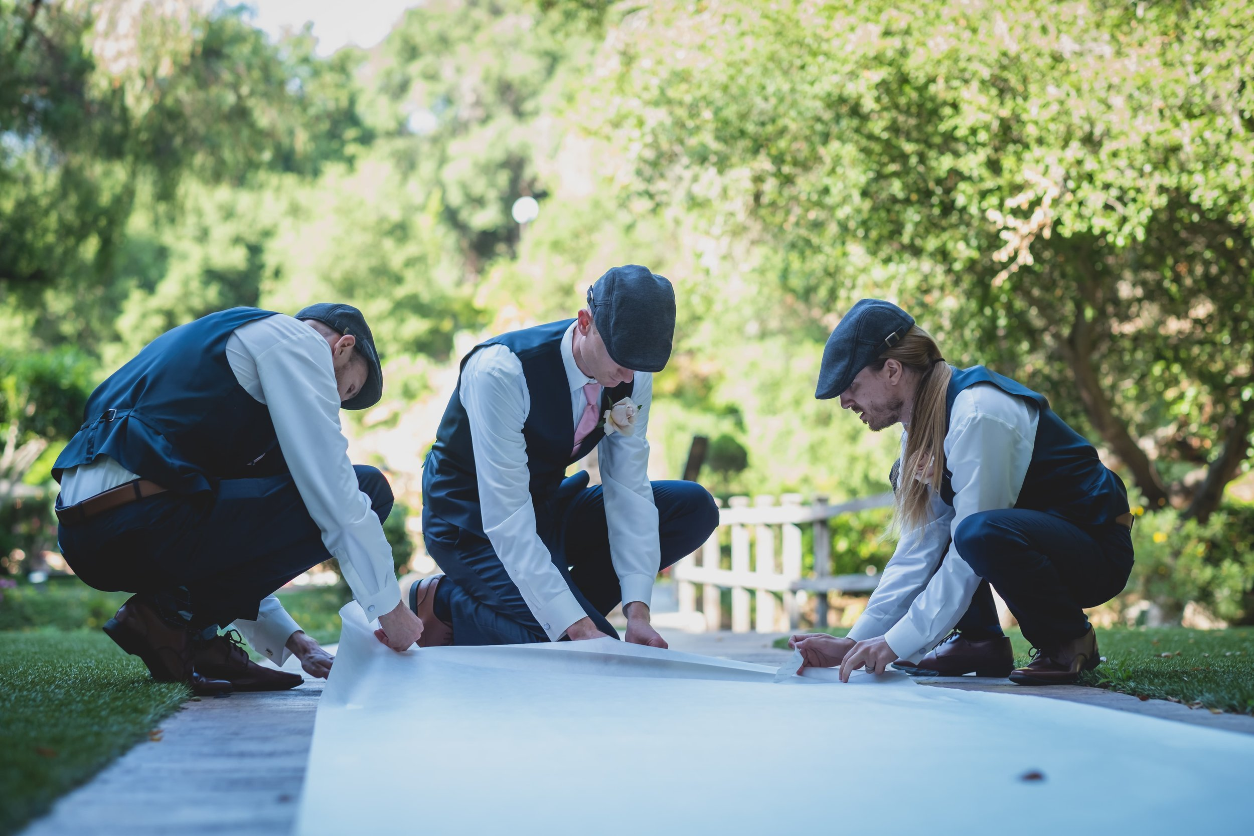 How To Keep Your Bridal Party Informed: A Guide To Keeping Everyone In The Loop - Groomsman helping decorate for the ceremony.