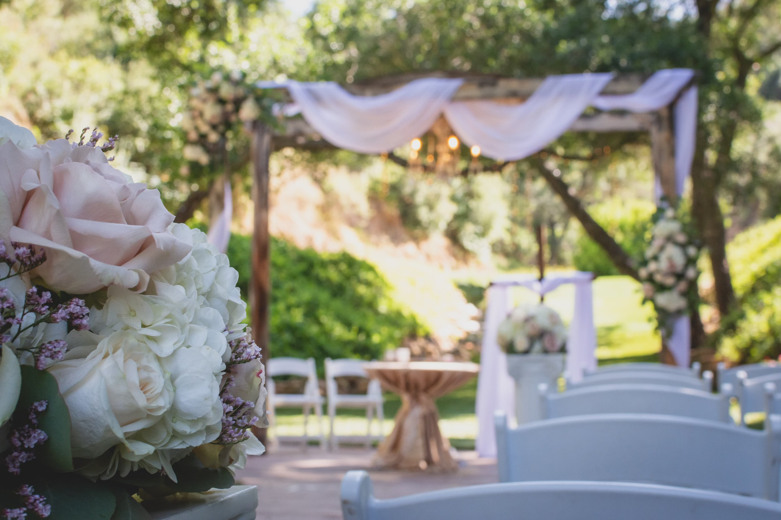 How To Keep Your Bridal Party Informed: A Guide To Keeping Everyone In The Loop - An arched ceremony altar decorated with flowers, greenery, and pink cloth.