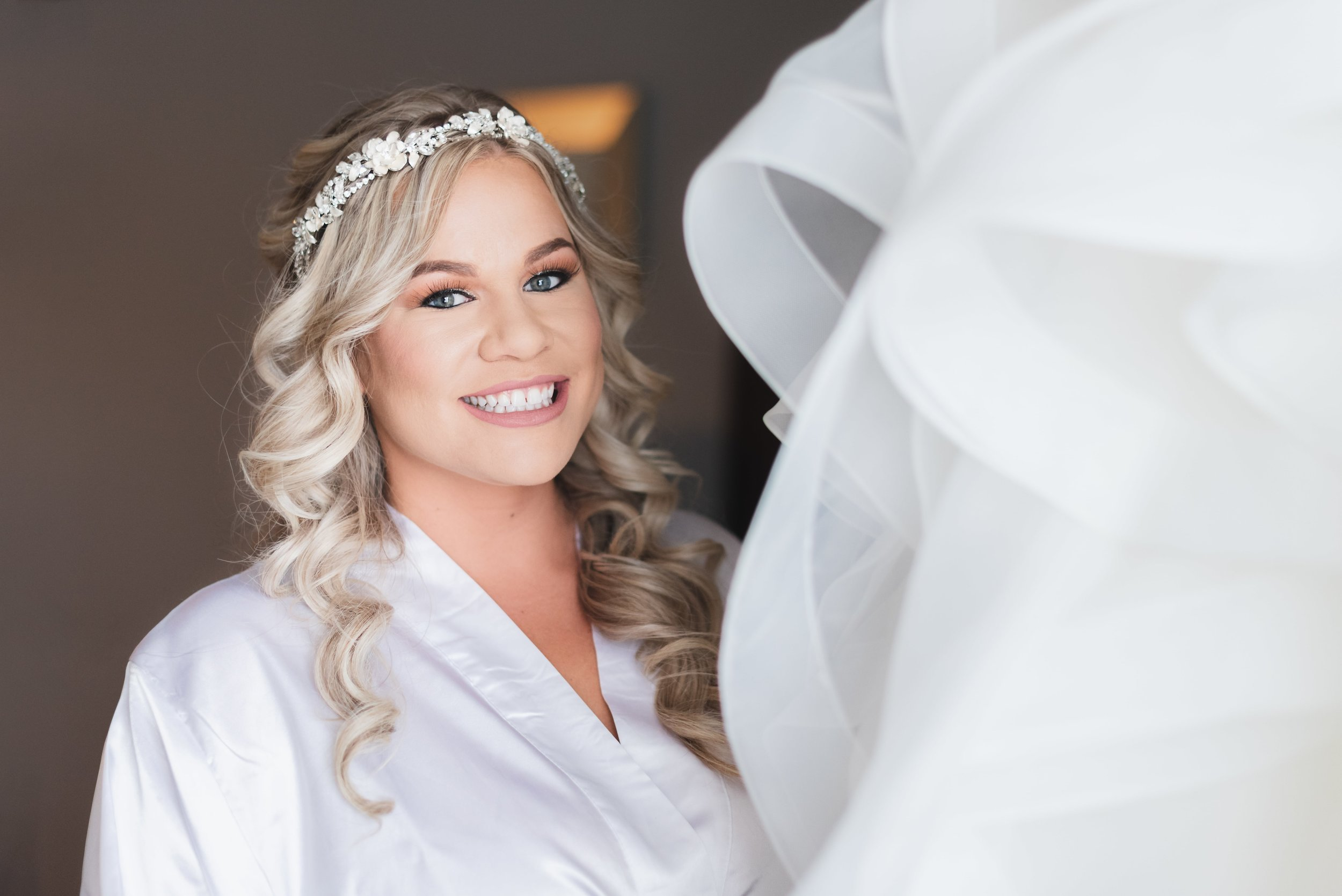 Bride smiling on the morning of her wedding day.