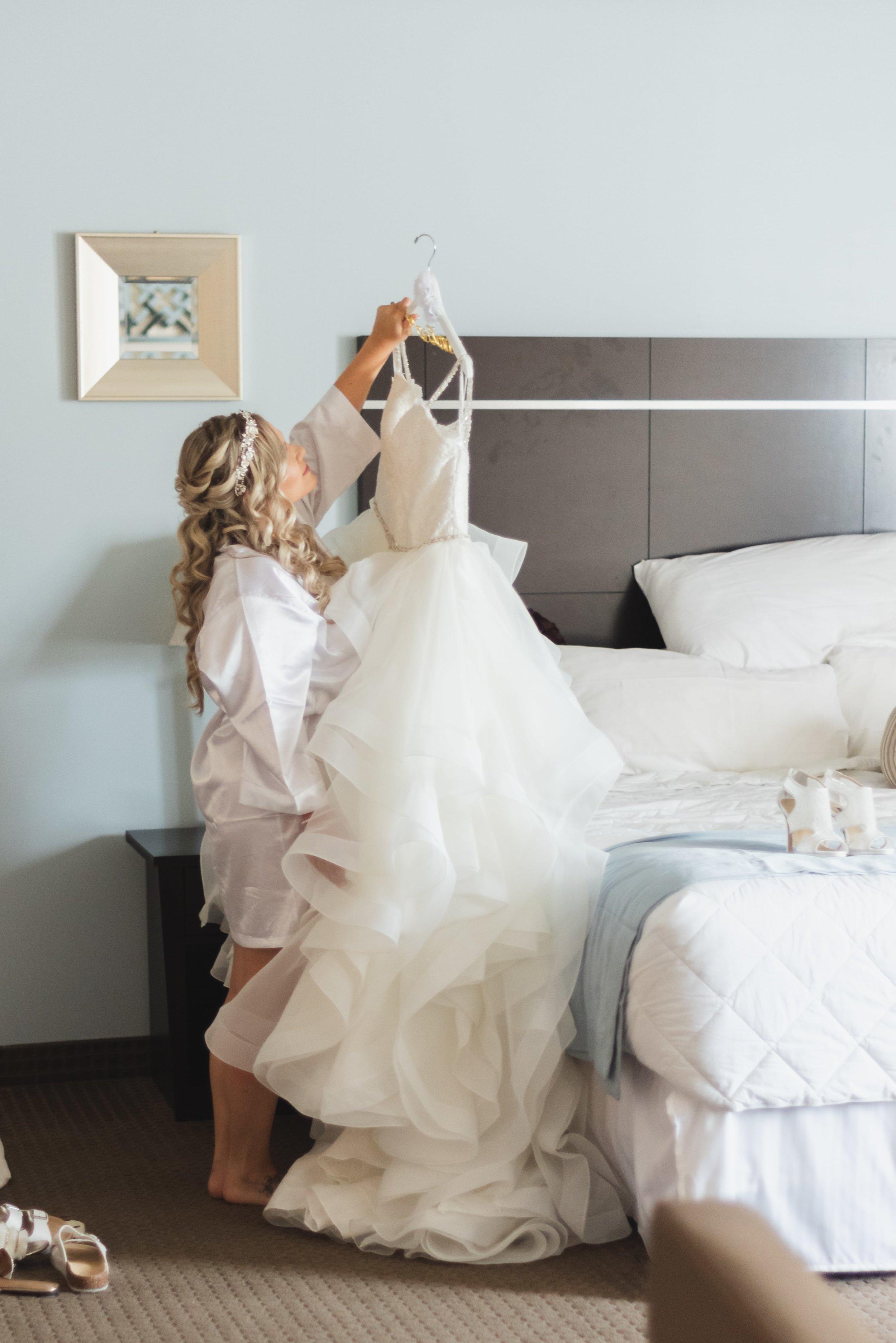 Bride lifting her wedding dress in her hotel room.