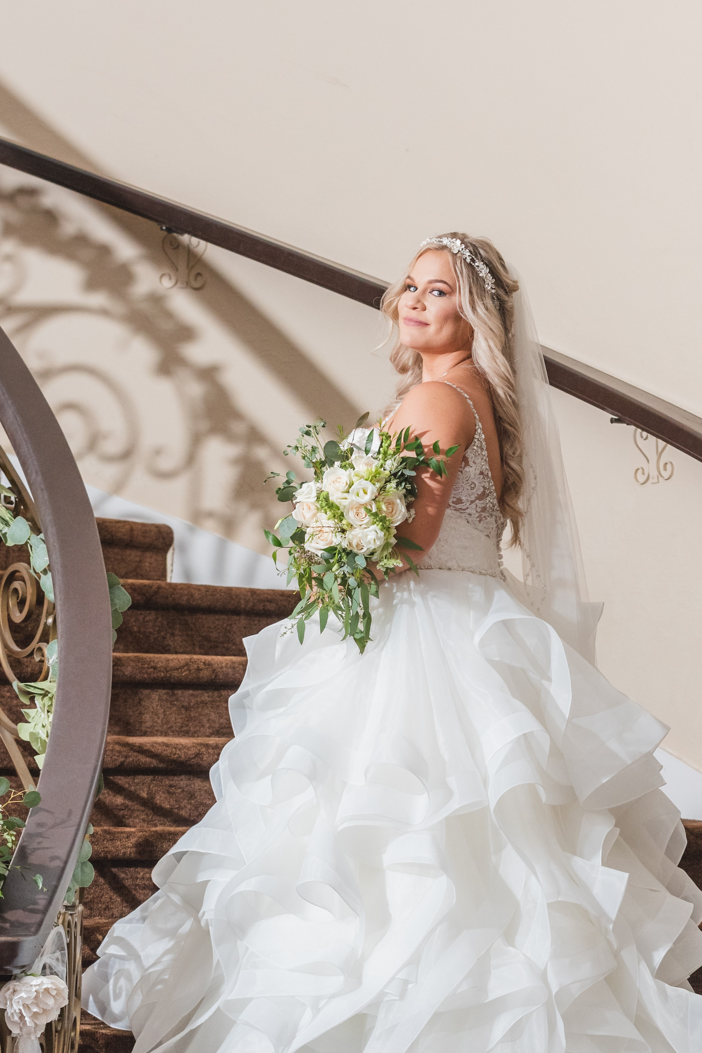 Bride in her wedding dress looking back over her shoulder as she climbs a curving staircase.