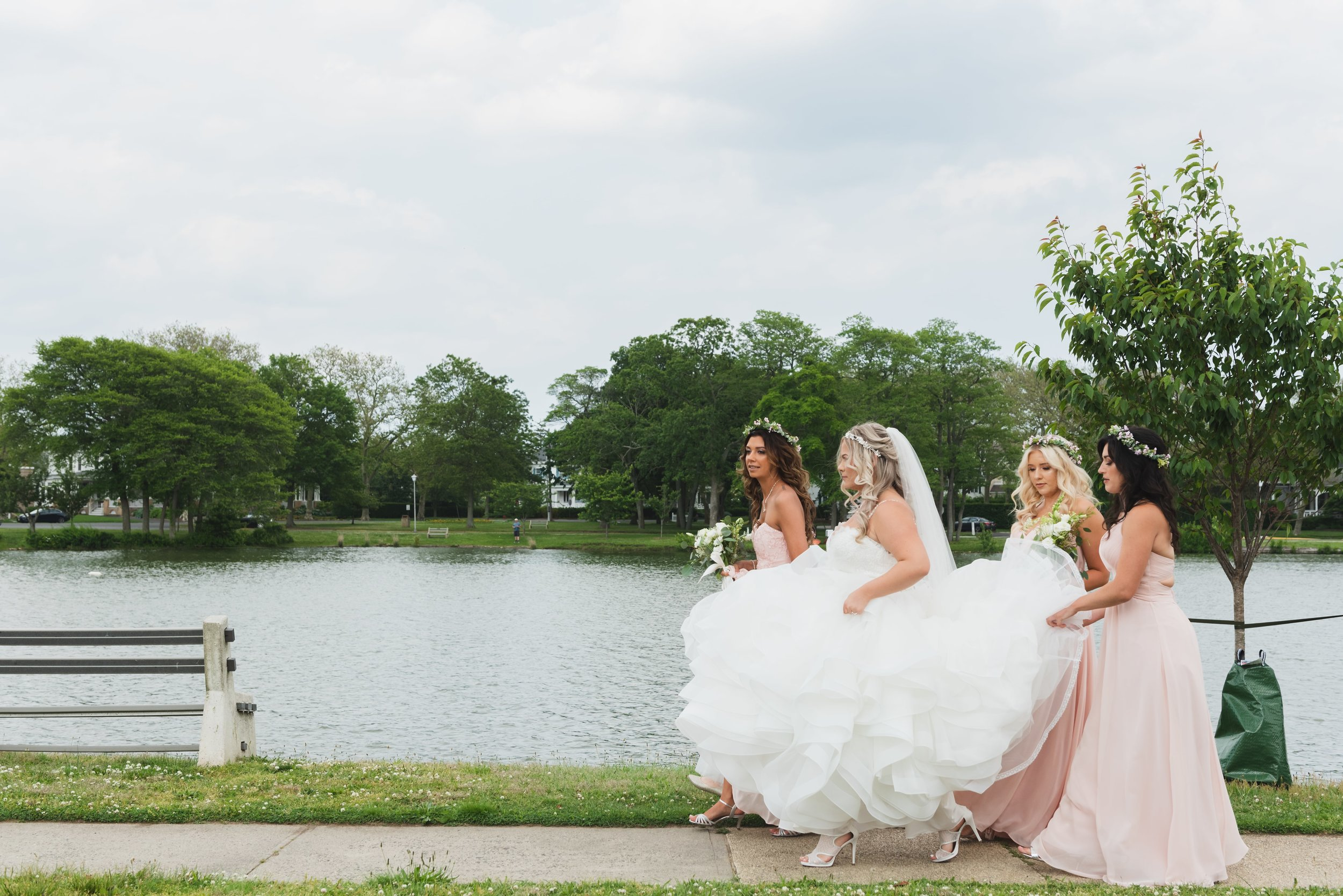 Bride on her way to the first look with her bridesmaids holding her trailing dress.