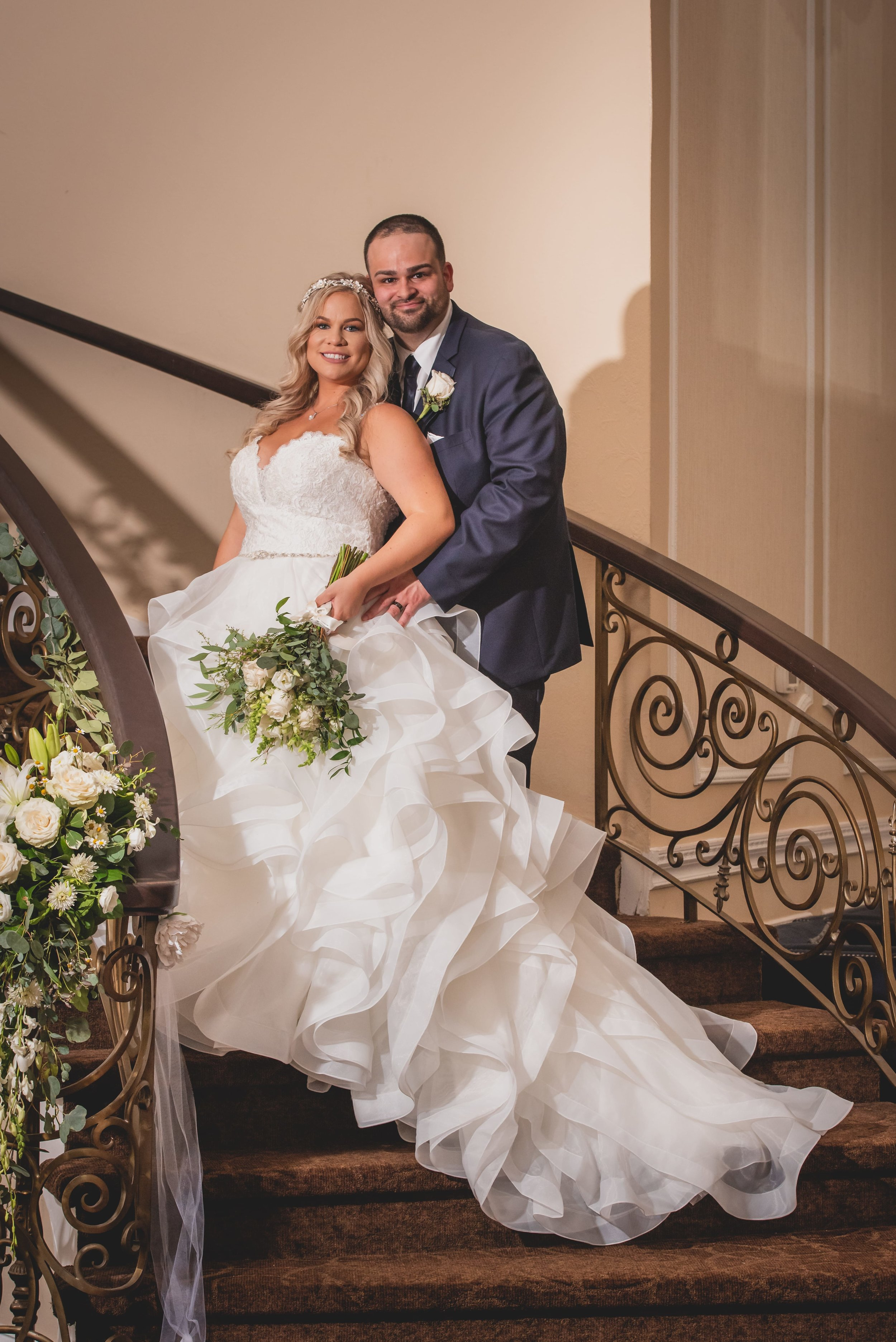 Bride and groom smiling on a curving staircase.